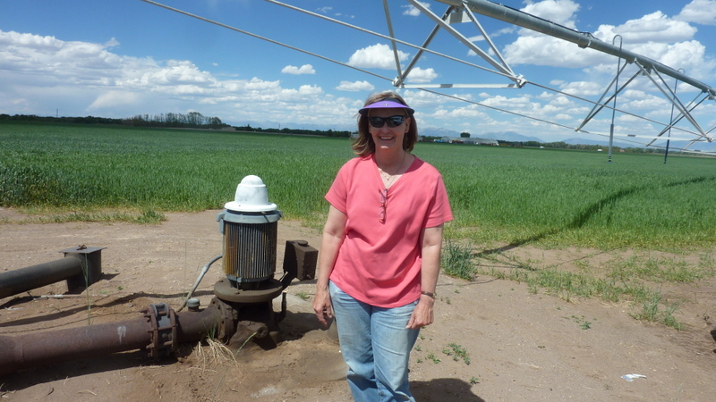 Karla Shriver stands by one of the many pivot sprinkler systems that she uses to irrigate her farm, just north of Alamosa. She irrigates her land with water from ditches and the aquifer, and is concerned about the depletion of the aquifer.