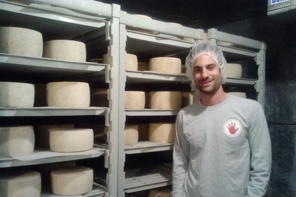 John Scaggs with Haystack Mountain Goat Dairystands beside aging cheese. Scaggs' company has started using the state's new Colorado branding.