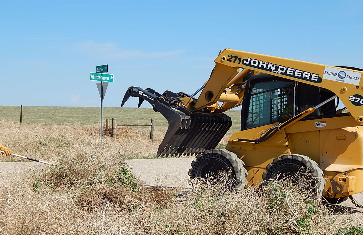 A Skid Steer Loader pulls tumbleweed out of a ditch.
