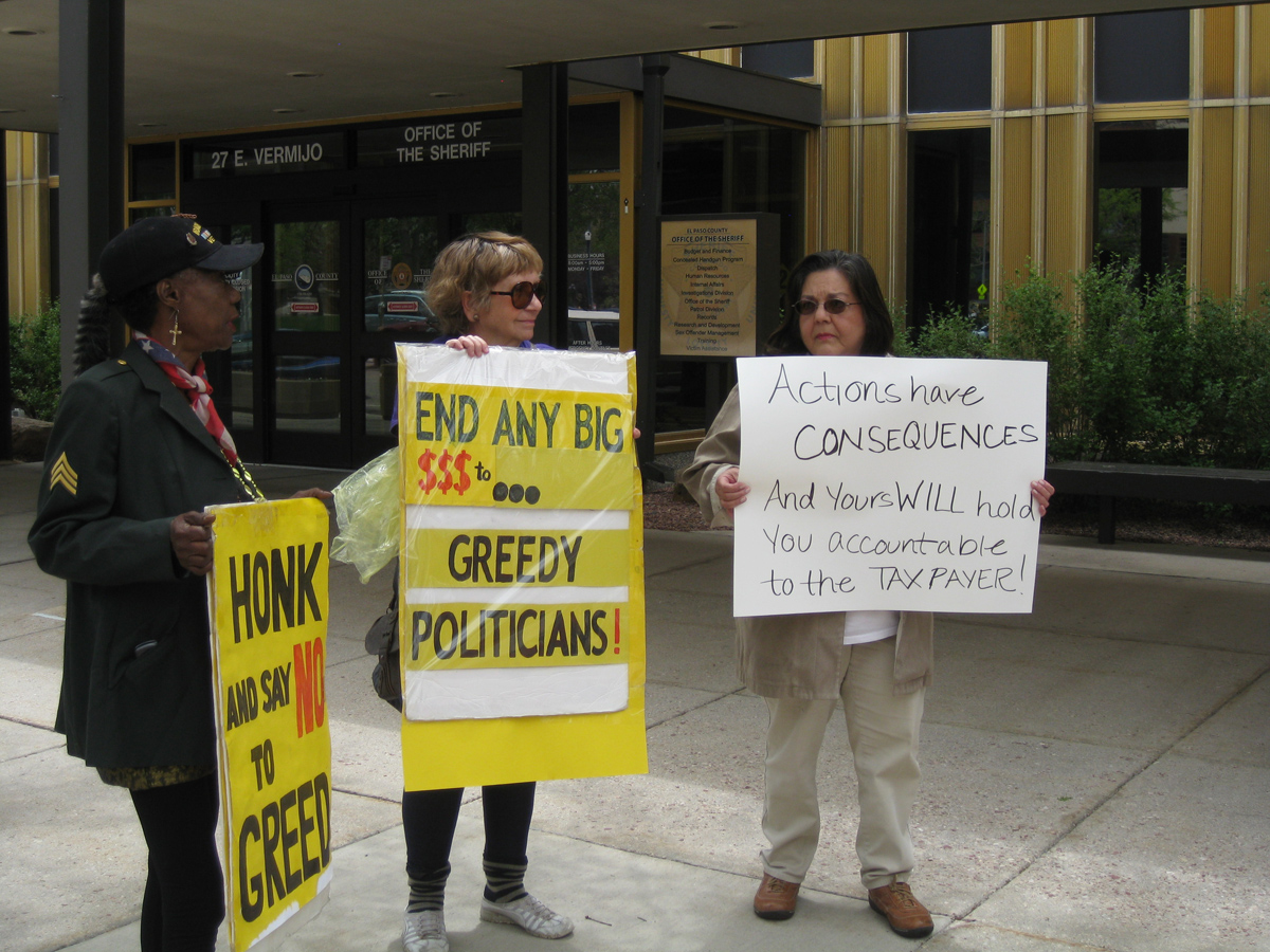 Critics of Sheriff Terry Maketa holds a sign outside the El Paso County Sheriff's Department