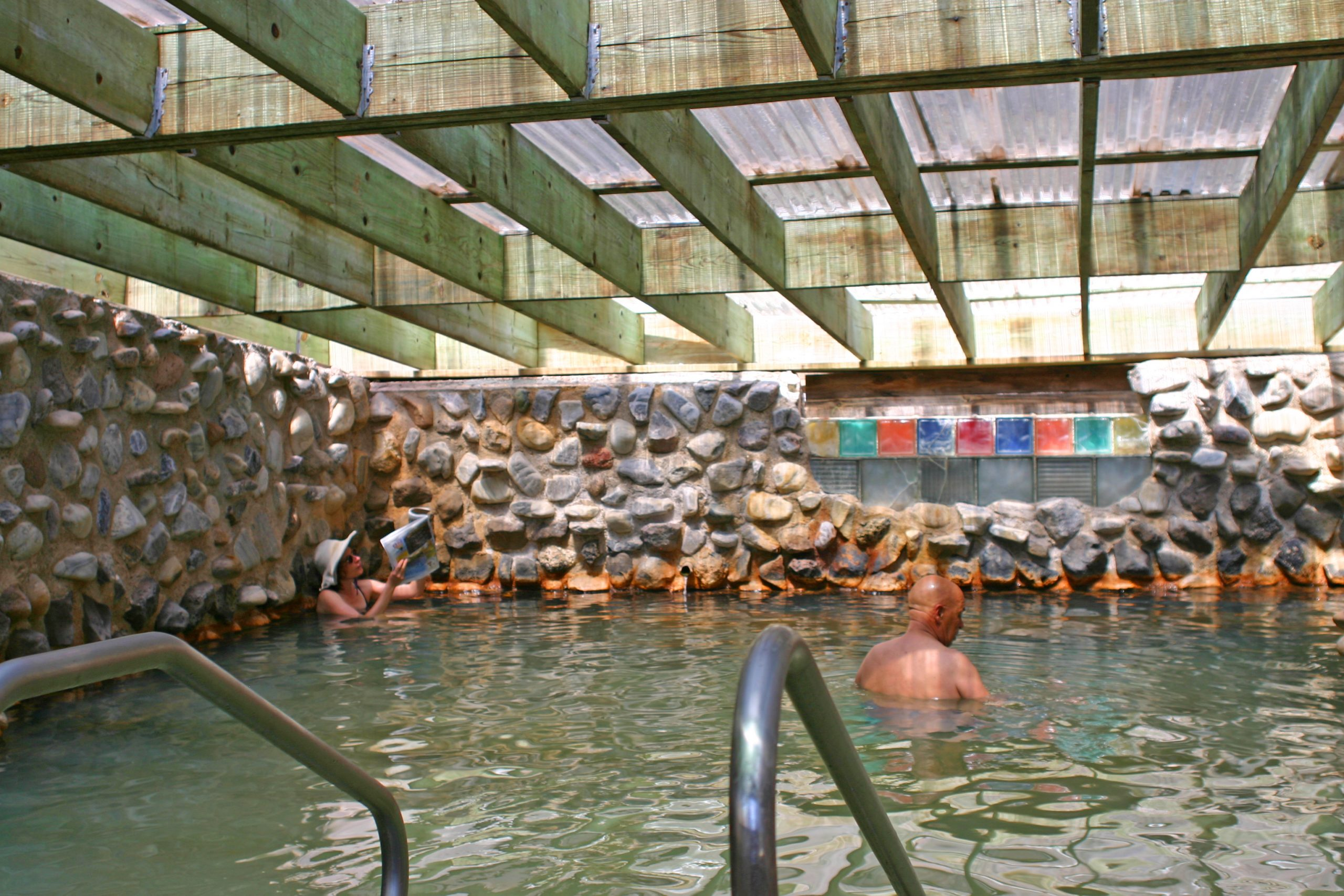 The soda springs pool at Ojo  is buoyant and covered by a greenhouse-style roof.
