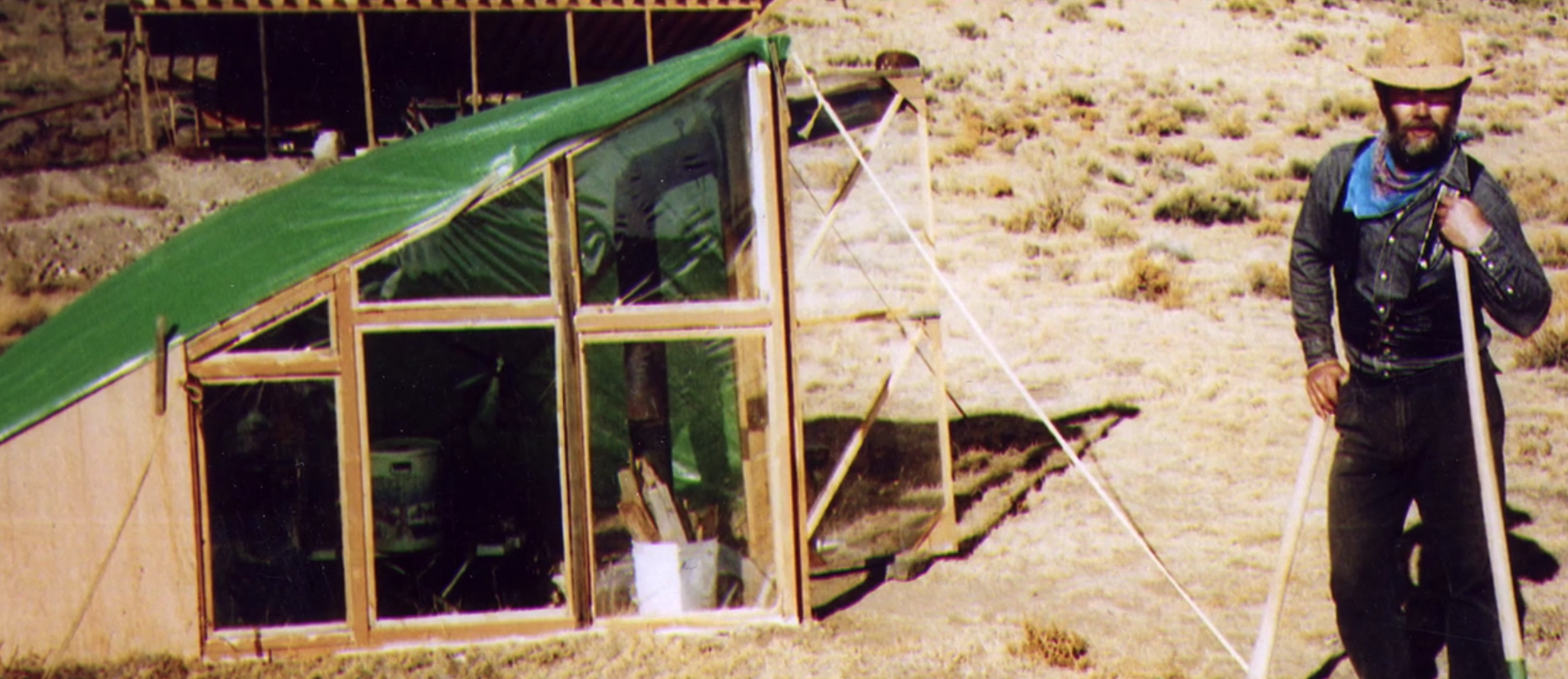 Mike Rust and the makeshift shelter he lived in while building his home by hand, ca. 1995