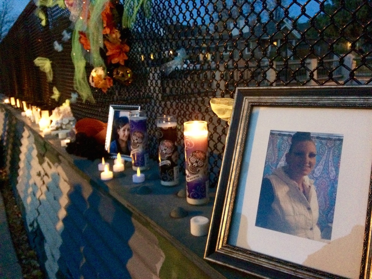 A bridge at a candlelight vigil was decorated with photos