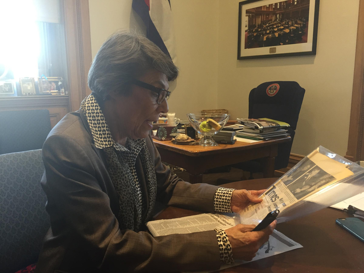State Senator Lucia Guzman reads a newspaper article about her father's murder. She said his death inspired her to try to repeal the death penalty.