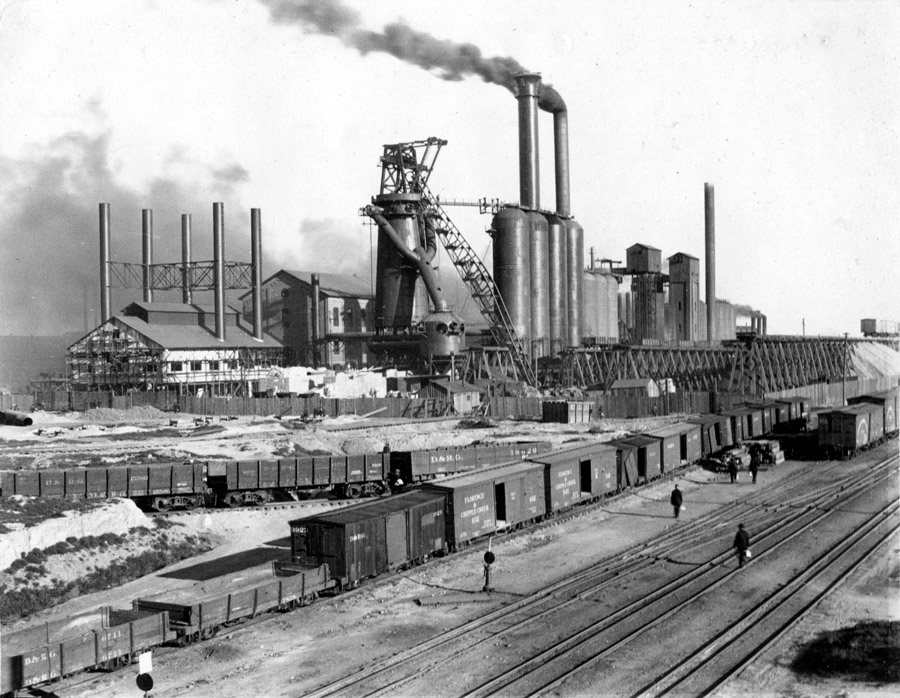 General view of the CF&I blast furnace row and rail yard before the steel mill was fenced. Denver and Rio Grande rail cars are in the foreground. Date is unknown, but most likely in the 1910-1920s.
