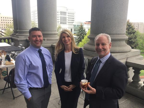 Reps. Patrick Neville (R-Castle Rock), Brittany Pettersen (D-Lakewood) and Dave Young (D-Greeley) celebrate on the Capitol balcony on closing day.