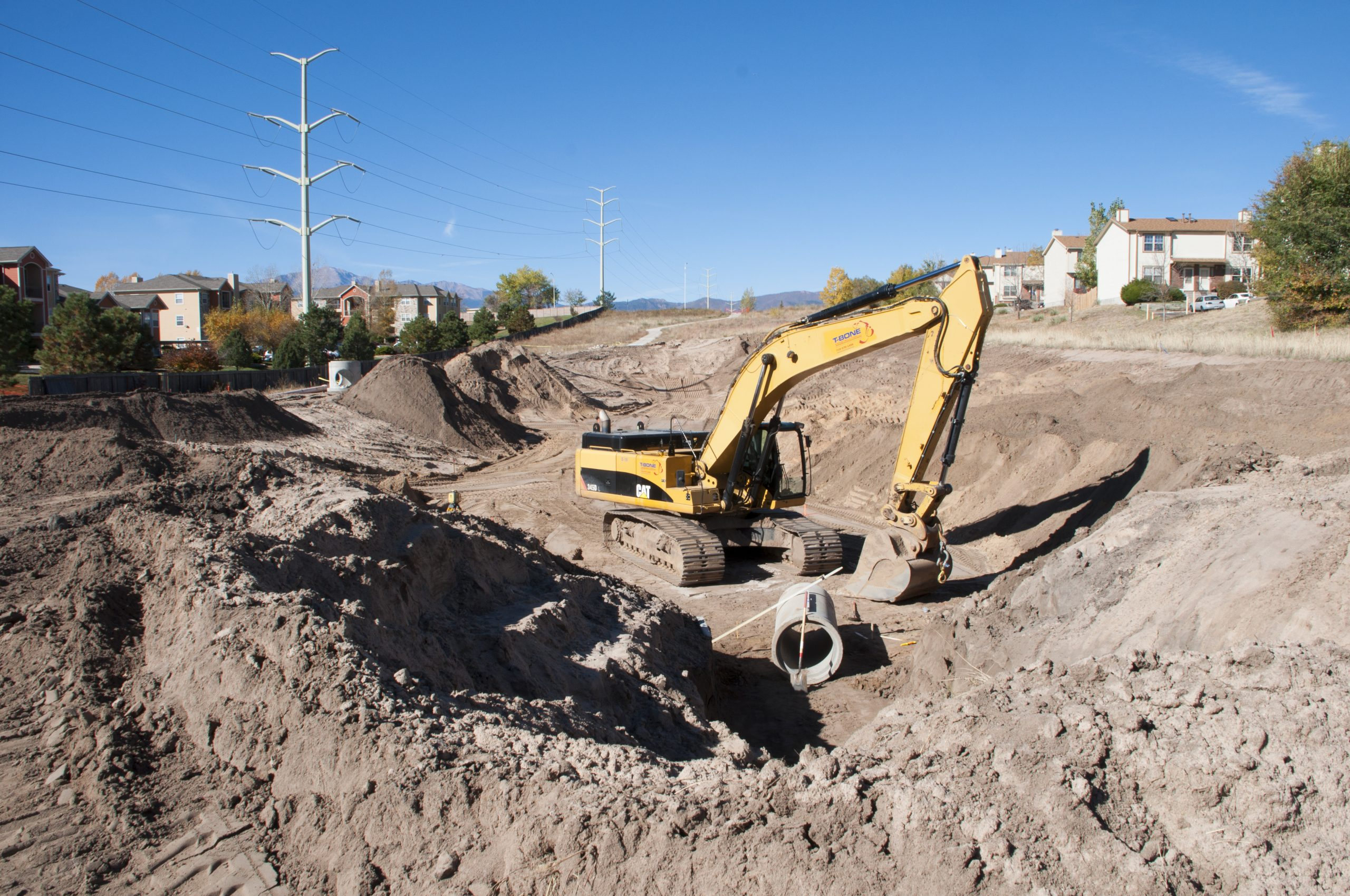 A construction crew works on a retention pond off Woodmen Road, one of 71 stormwater projects agreed to by the City of Colorado Springs as part of an intergovernmental agreement with Pueblo County.