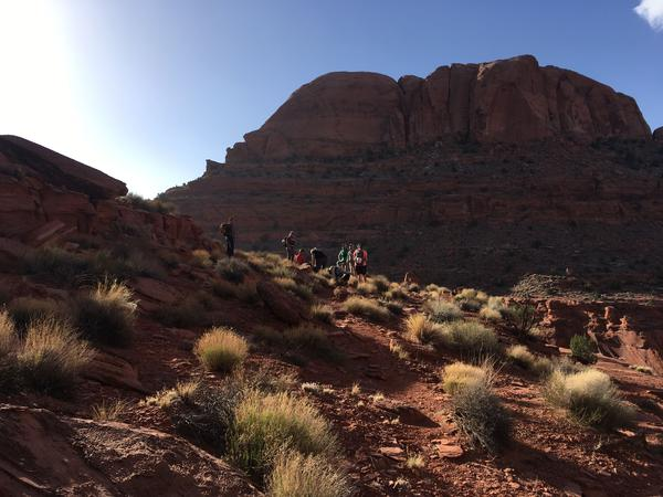 A group of canyoneers hikes across buttes and mesas to a slot canyon in Utah's Glen Canyon National Recreation Area, near the edge of Grand Staircase-Escalante National Monument.