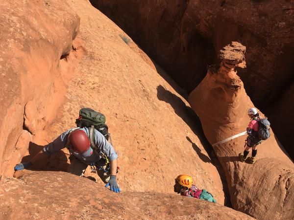 The group downclimbs a stretch of slickrock to rappel into the canyon. Once they pull the rope in behind them, the only way out is to follow the canyon until it loops back to trails along the Escalante River.