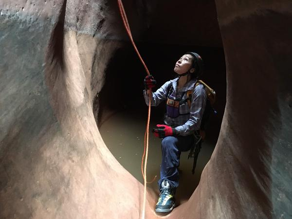 Saori Kado Barlow belays fellow canyoneers as they rappel deeper into the canyon.