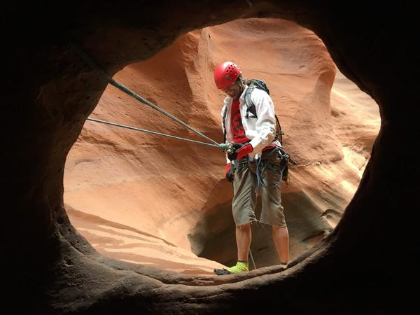 Tom Nief prepares for a rappel from ropes looped to the rock through a series of natural holes.