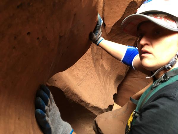 Brenda Lonnergan inspects the exit of Neon Canyon, which at first looks like a maze of rock leading to a dead end, except for a precipitous drop through a hole in the sandstone floor.
