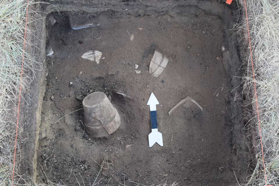The artifacts found at the site include broken pottery and an upside down flower pot.