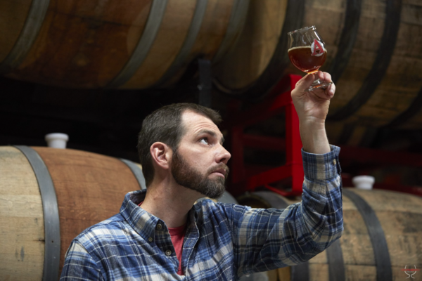 'Beer archaeologist' Travis Rupp inspects the latest ale of antiquity, George Washington Porter, surrounded by the oak barrels it fermented in at Avery Brewing Company in Boulder, Colo.
