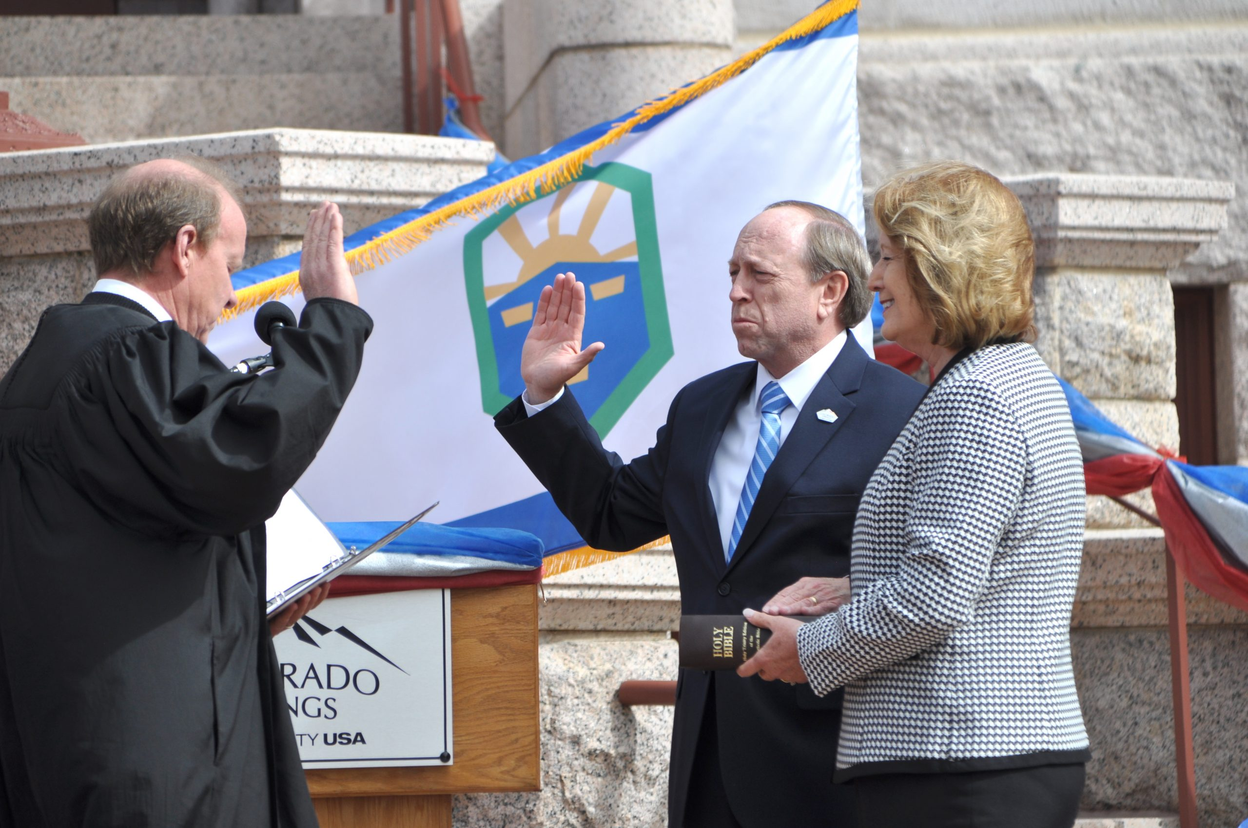 Judge HayDen Kane administers the oath of office to Colorado Springs mayor John Suthers, who is joined by first lady Janet Suthers.