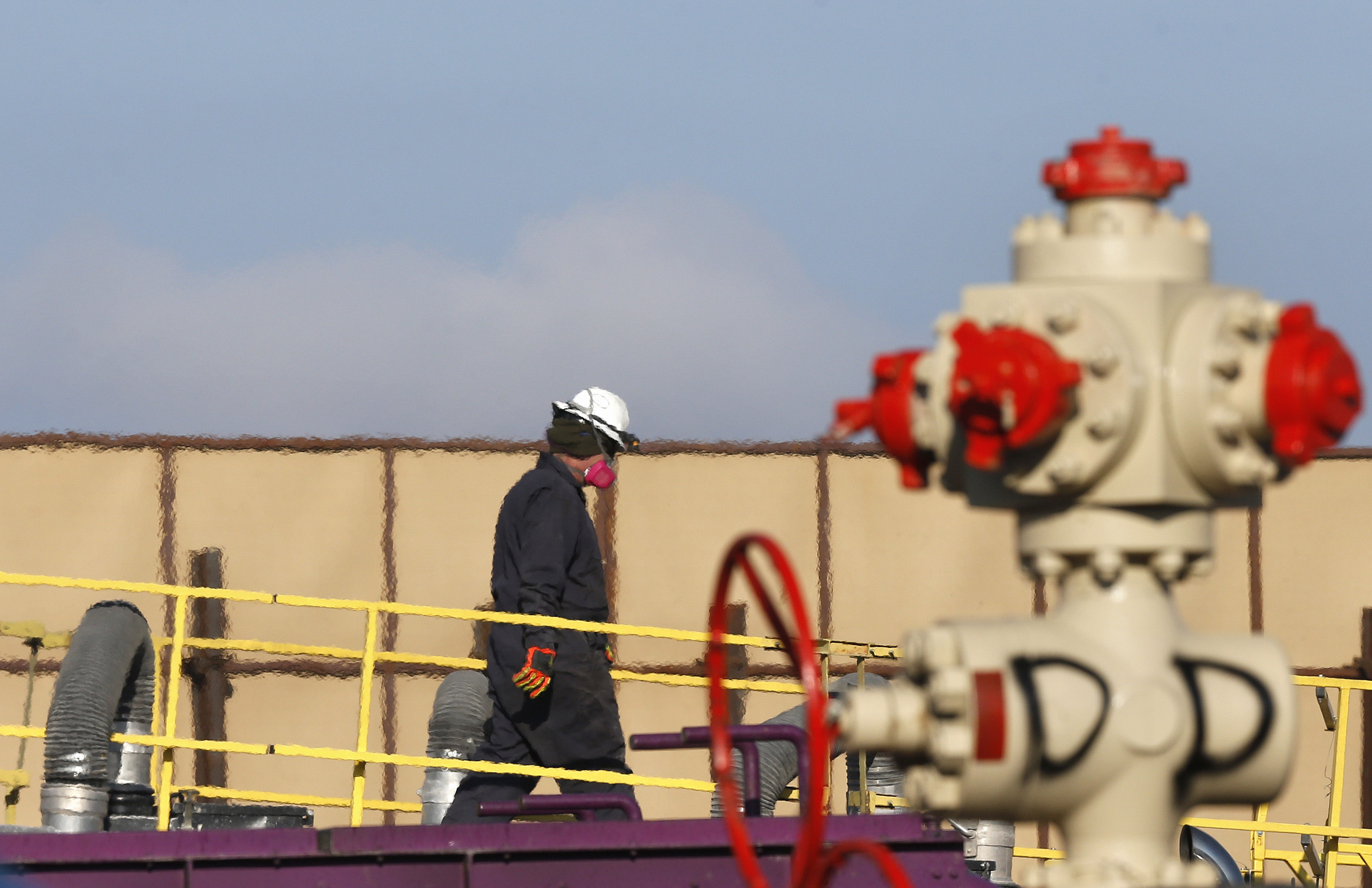 <p>In this March 25, 2014 photo, heat from machinery distorts the air as a worker watches over a hydraulic fracturing operation at an Encana Corp. oil well near Mead in Weld County, Colorado.</p>