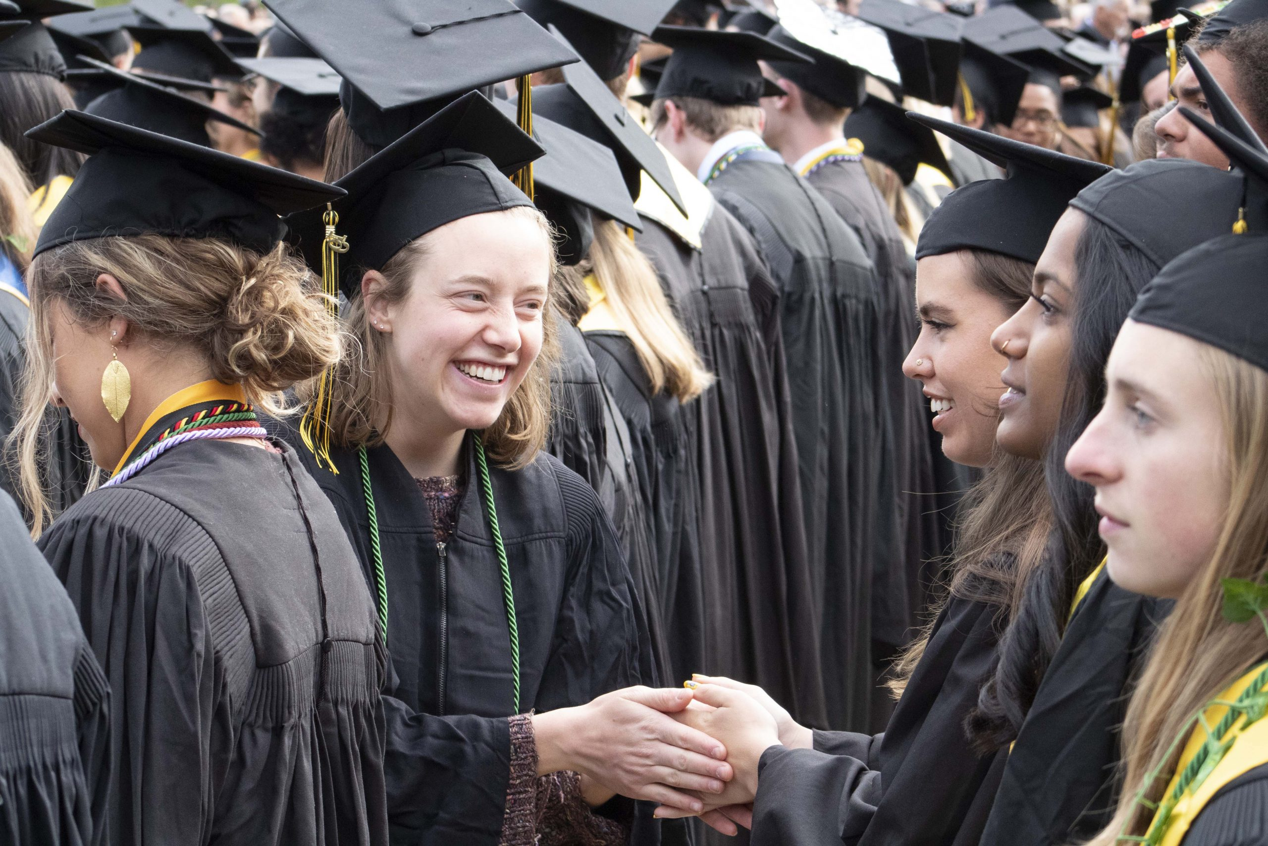 Graduates greet each other during commencement.