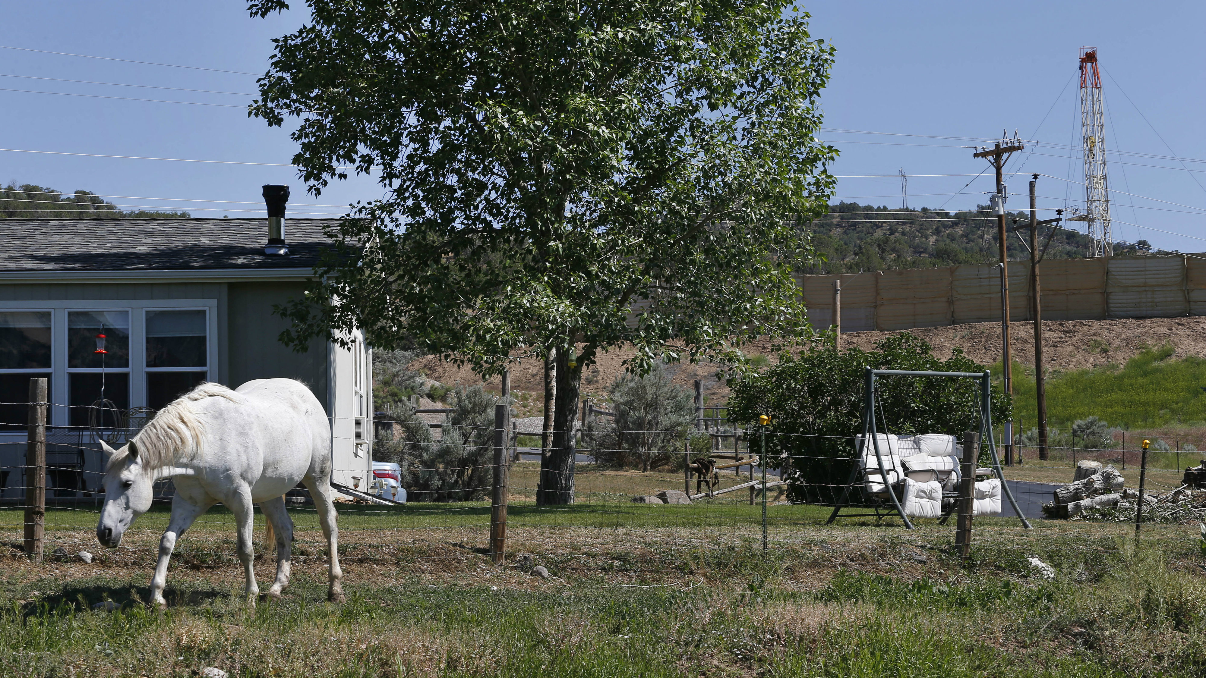 <p>This photo taken June 9, 2014 shows a horse named Primo grazing in front of the home of local resident Joann Aramillo, with an oil and gas rig on a well pad visible a few hundred yards away, top right, in New Castle, a small farming and ranching settlement on the Western Slope of the Rockies, in Colo.</p>