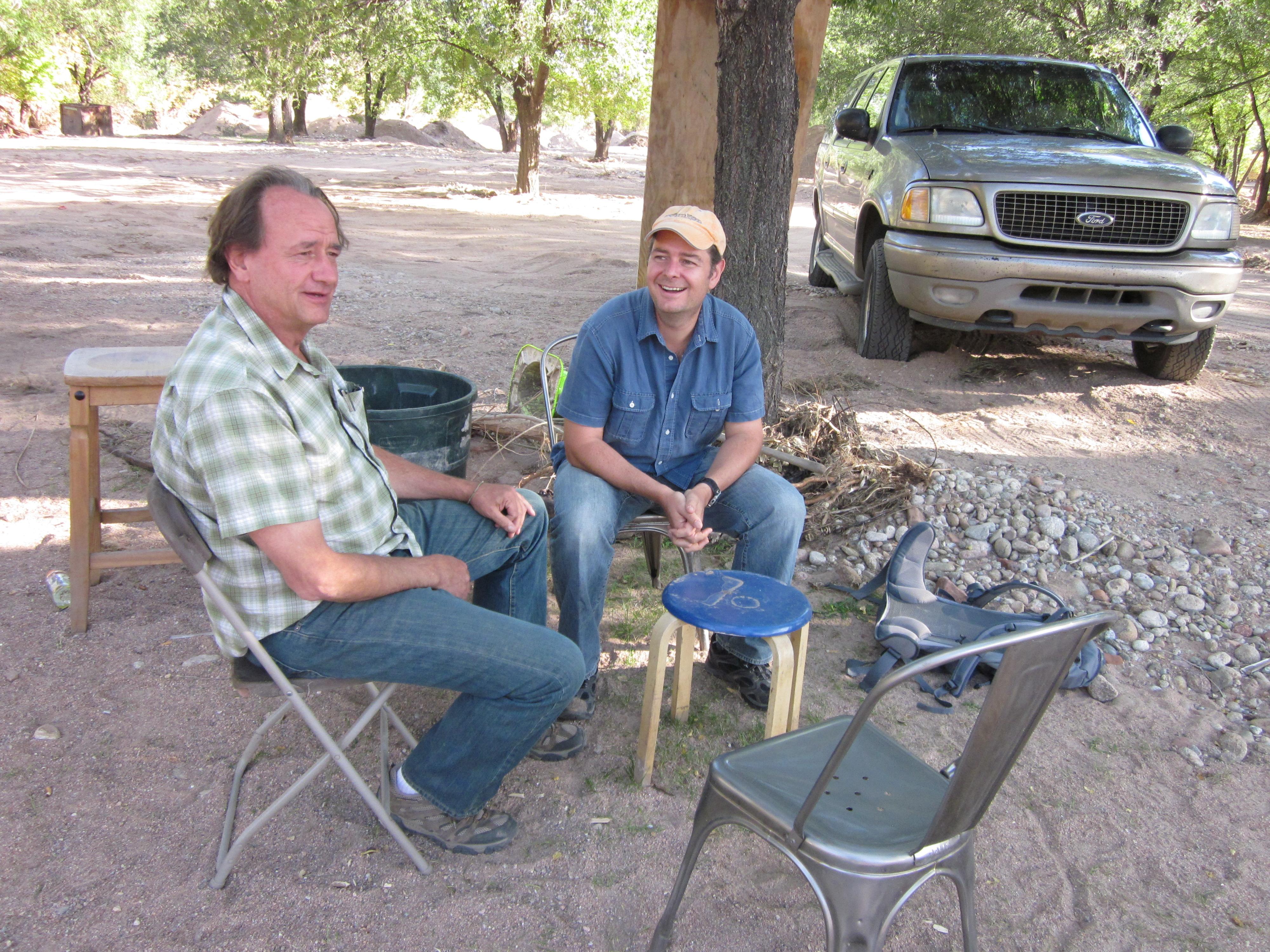 <p>Craig Ferguson, left, and Brian Eister hold a meeting al fresco at Planet Bluegrass.</p>