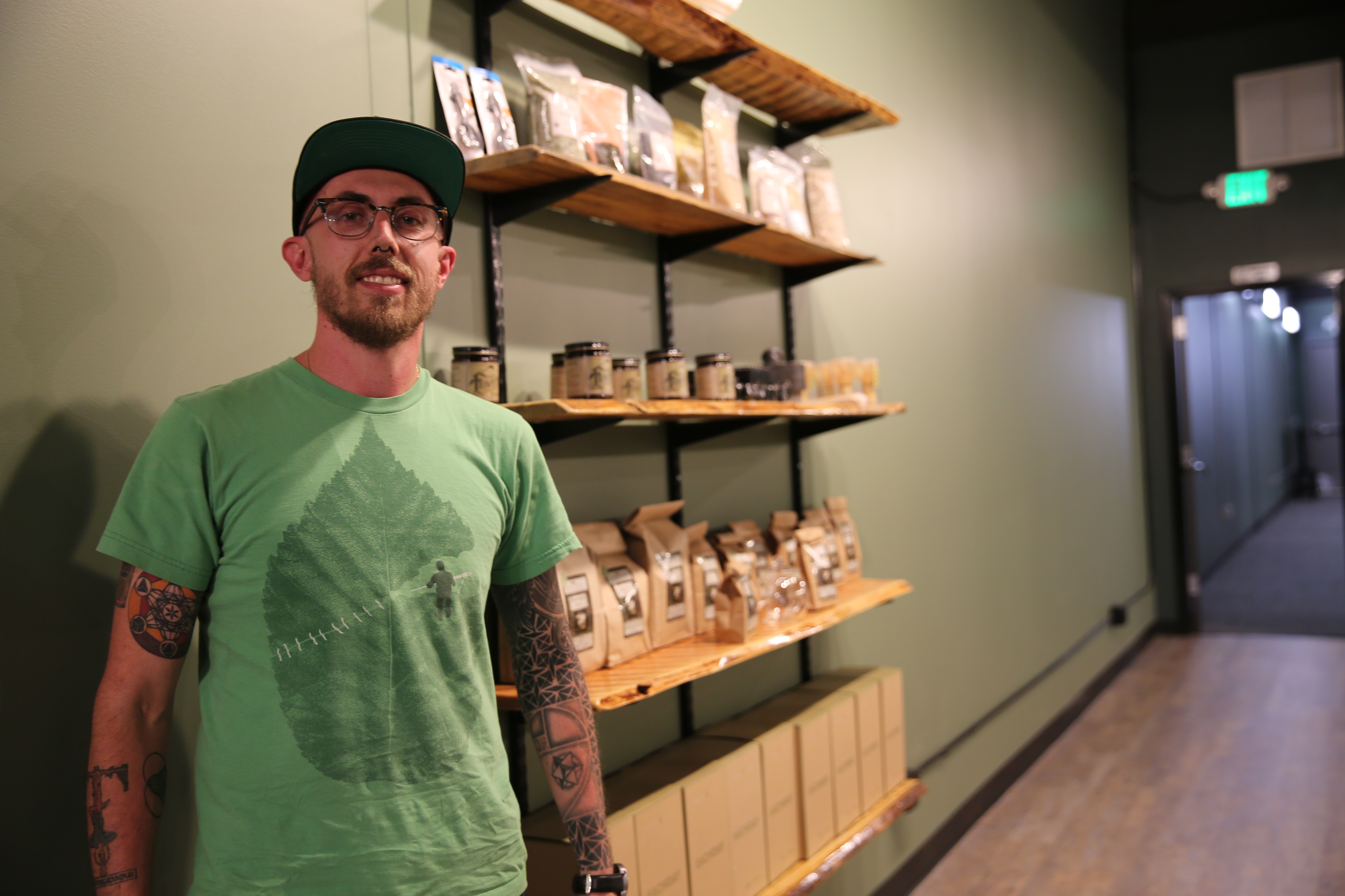 <p>Jeremy Haley, the owner of Rocky Mountain Kratom, stands in front of a display at his new store, Artisans Apothecary, on Broadway and Alameda. </p>