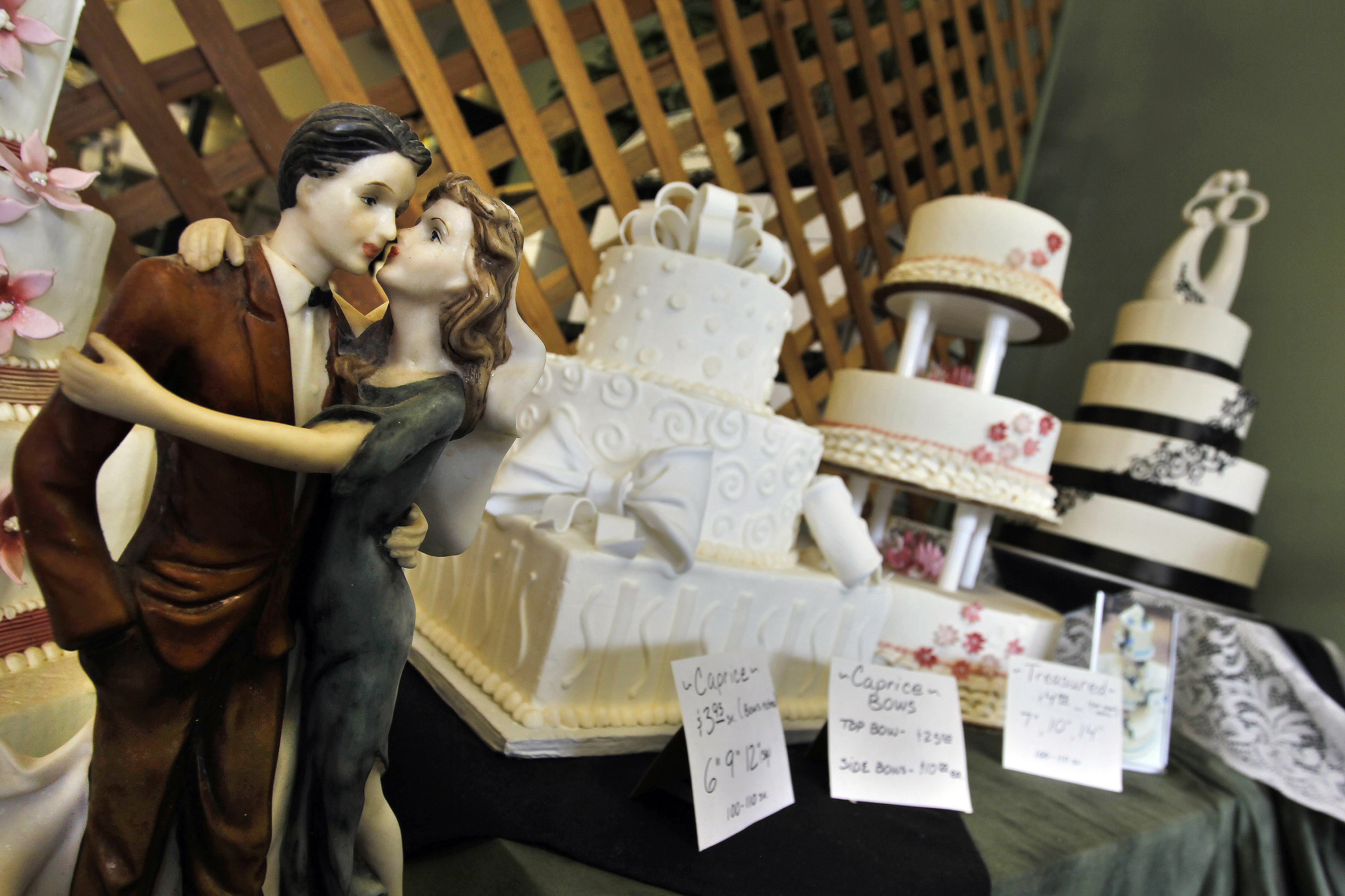 <p>Figurines are depicted in an embrace as part of the wedding cake display at Masterpiece Cakeshop in Denver, Thursday, June 6, 2013.</p>