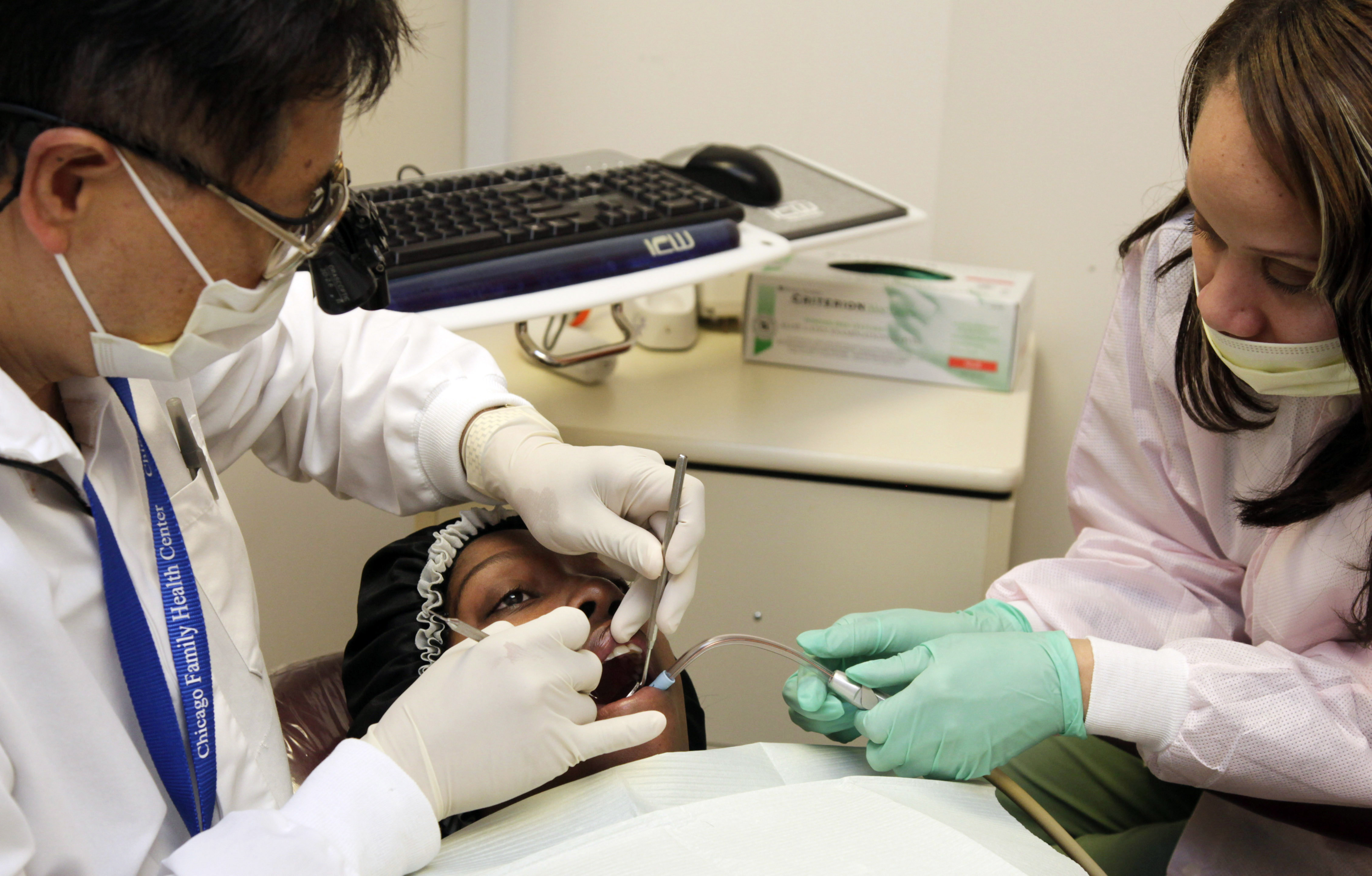 <p>Dentist Dr. Francis Tham and dental assistant Latasha Johnson attend to Medicaid patient Pamela Scott at the Chicago Family Health Center in Chicago.</p>