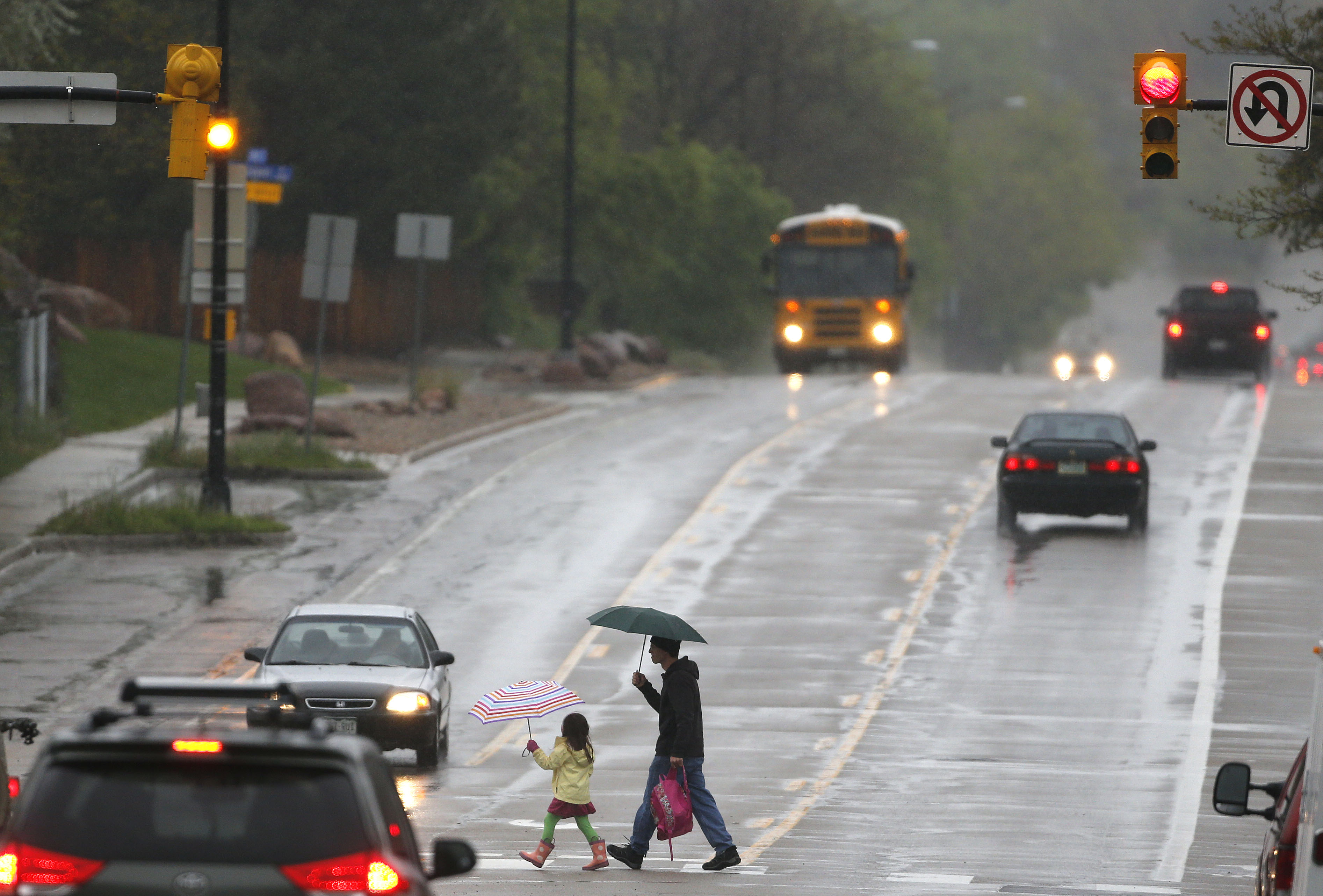 A man walks a student to school in the rain, in Boulder, Colo., Tuesday, May 19, 2015. Colorado braced for a spring storm with unseasonably heavy rains and several inches of snow expected in the high country.