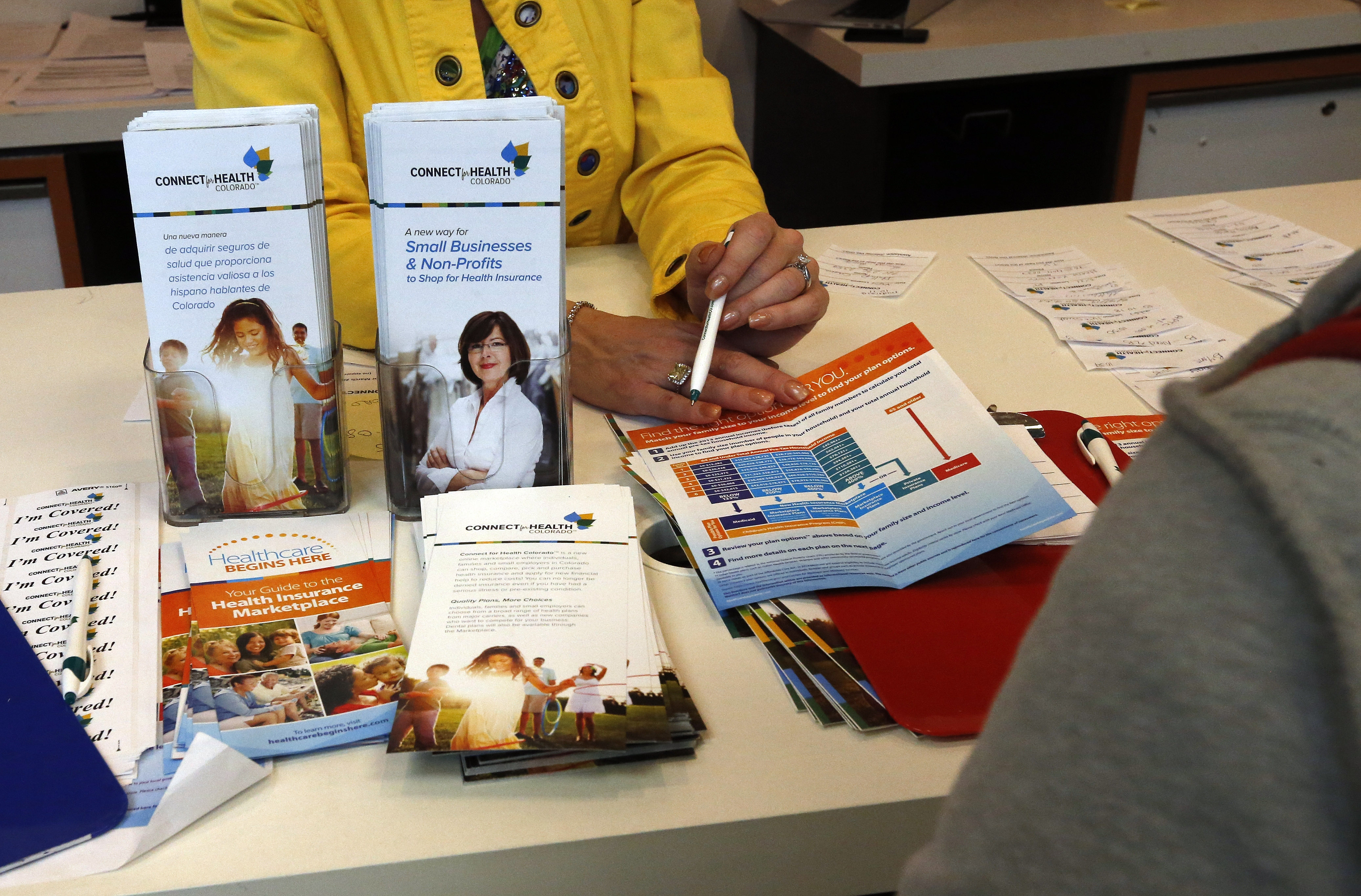 <p>An employee of Connect For Health Colorado, the state's health care exchange, explains options and procedures to a walk in client signing up for insurance, in Denver, Monday March. 31, 2014.</p>
