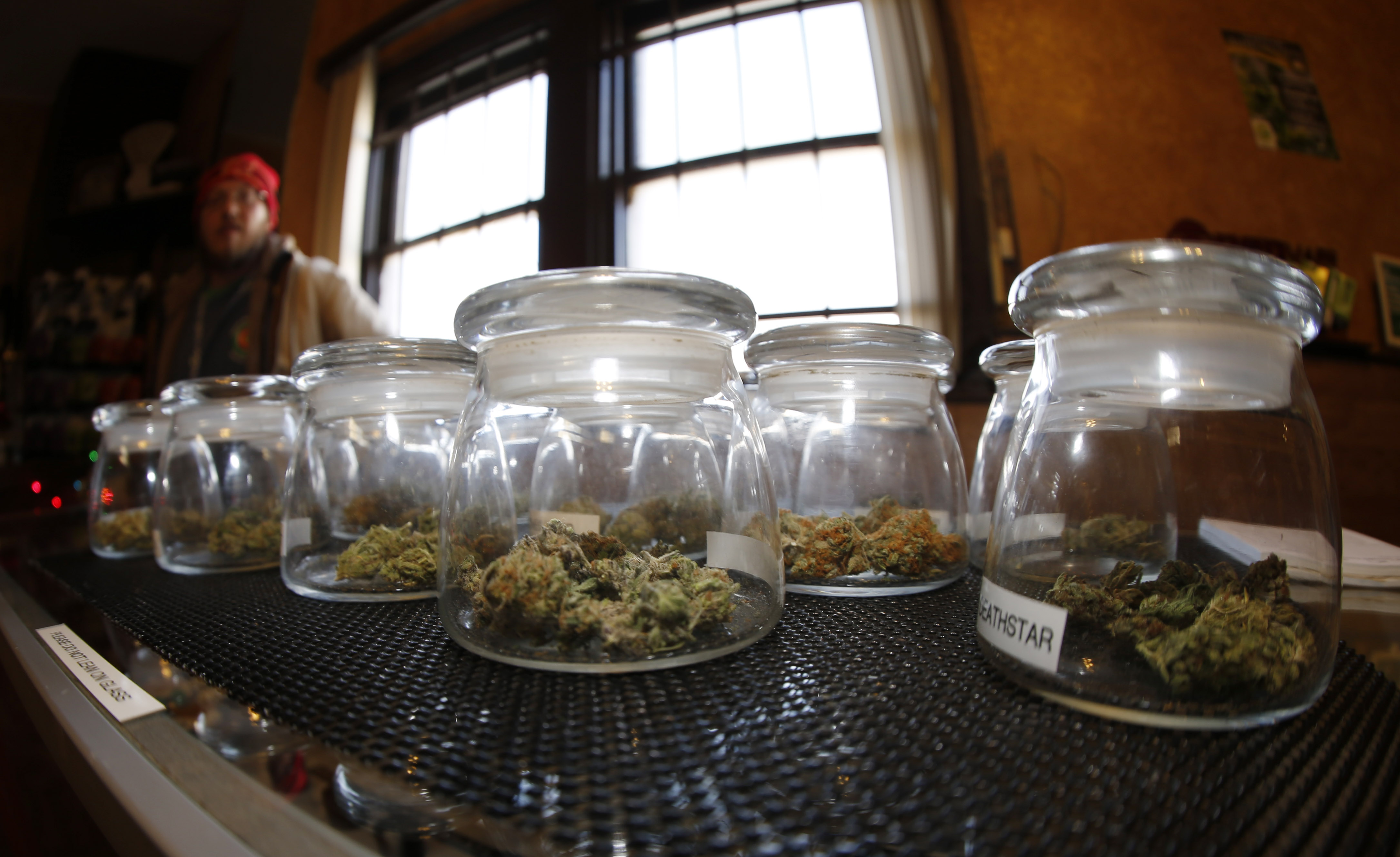 <p>Glass jars containing various strains of marijuana sit on a counter as sales associate Mattt Hart works at the 3D Dispensary on Friday, Dec. 19, 2014, in Denver.</p>
