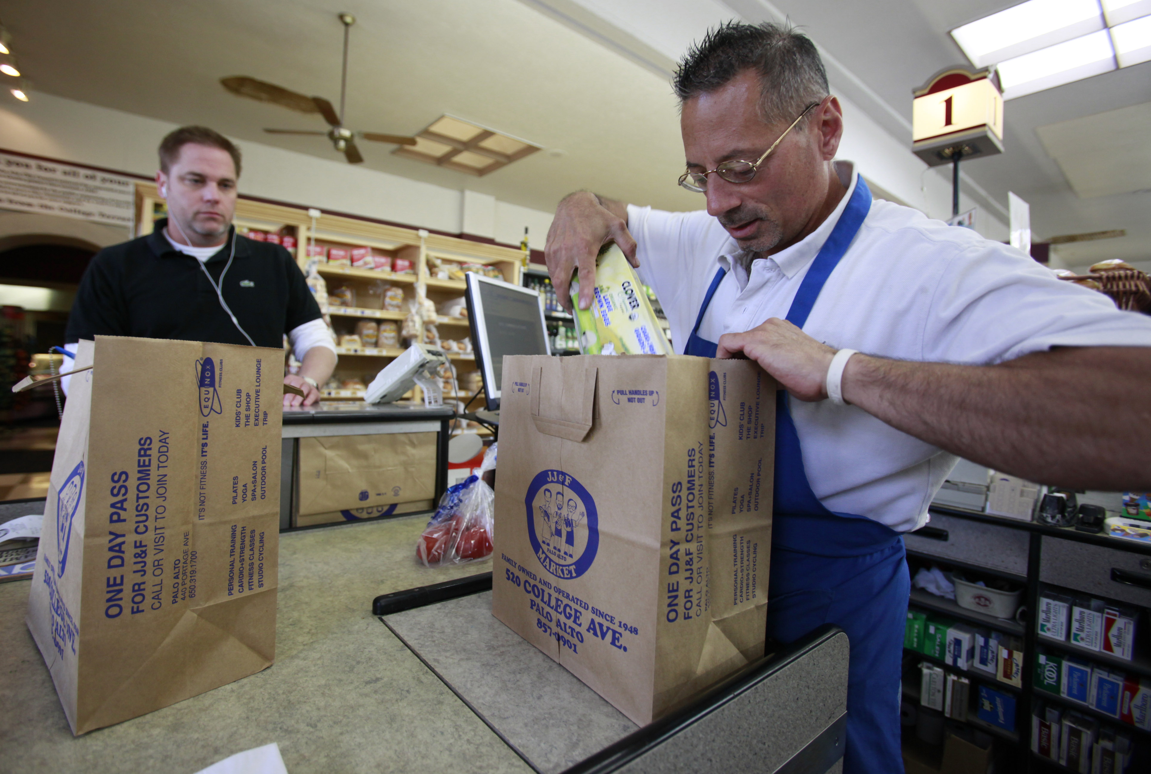 <p>A storeclerk bags groceries in a file photo. The city of Aspen has successfullydefended an ordinance that bans plastic bags and charges customers 20 cents for paper bags. Anti-tax advocates had argued that it ran afoul of the Colorado Taxpayer's Bill of Rights.</p>