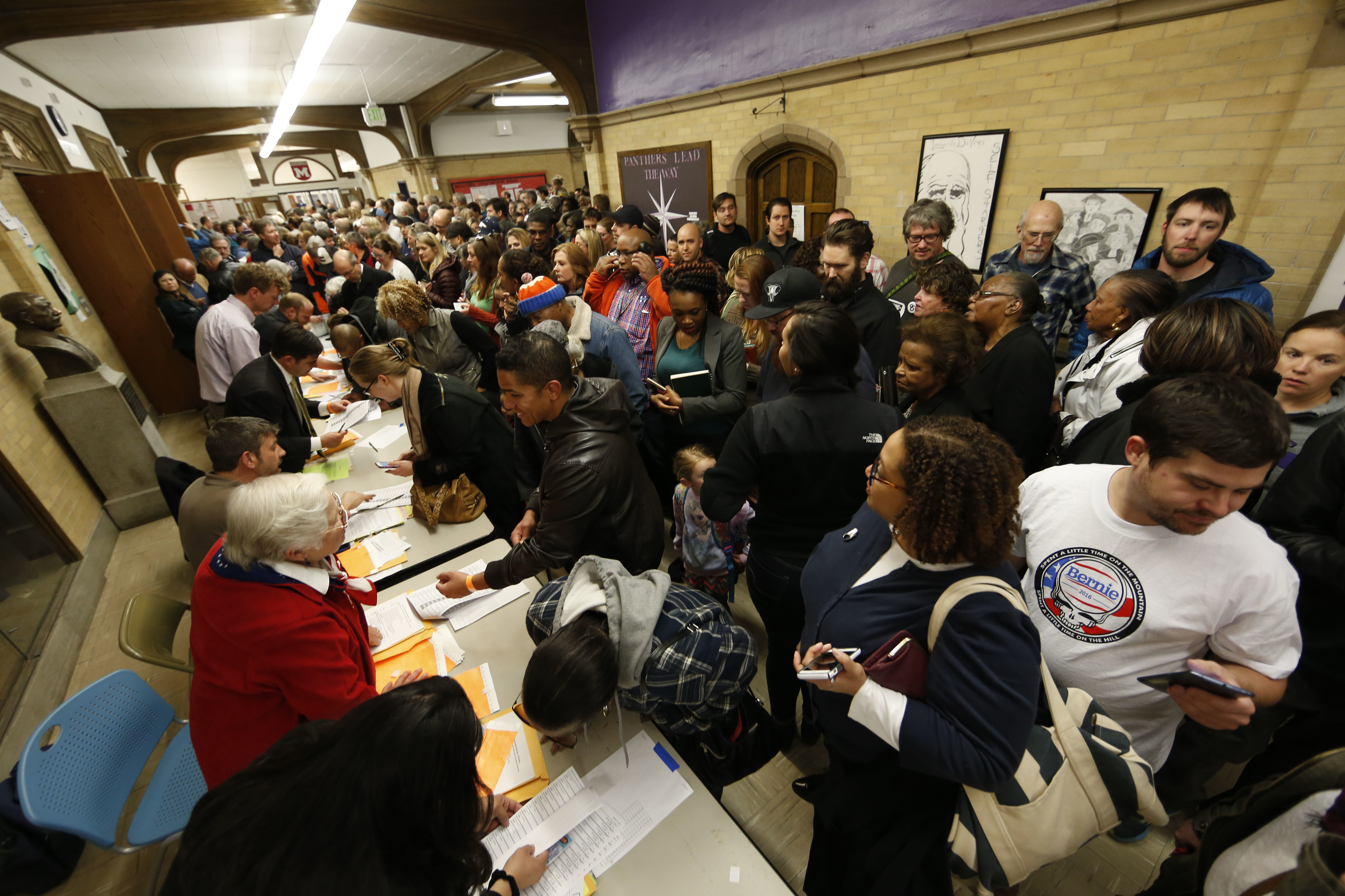 Voters arrive at a Democratic caucus Tuesday, March 1, 2016, in Denver.