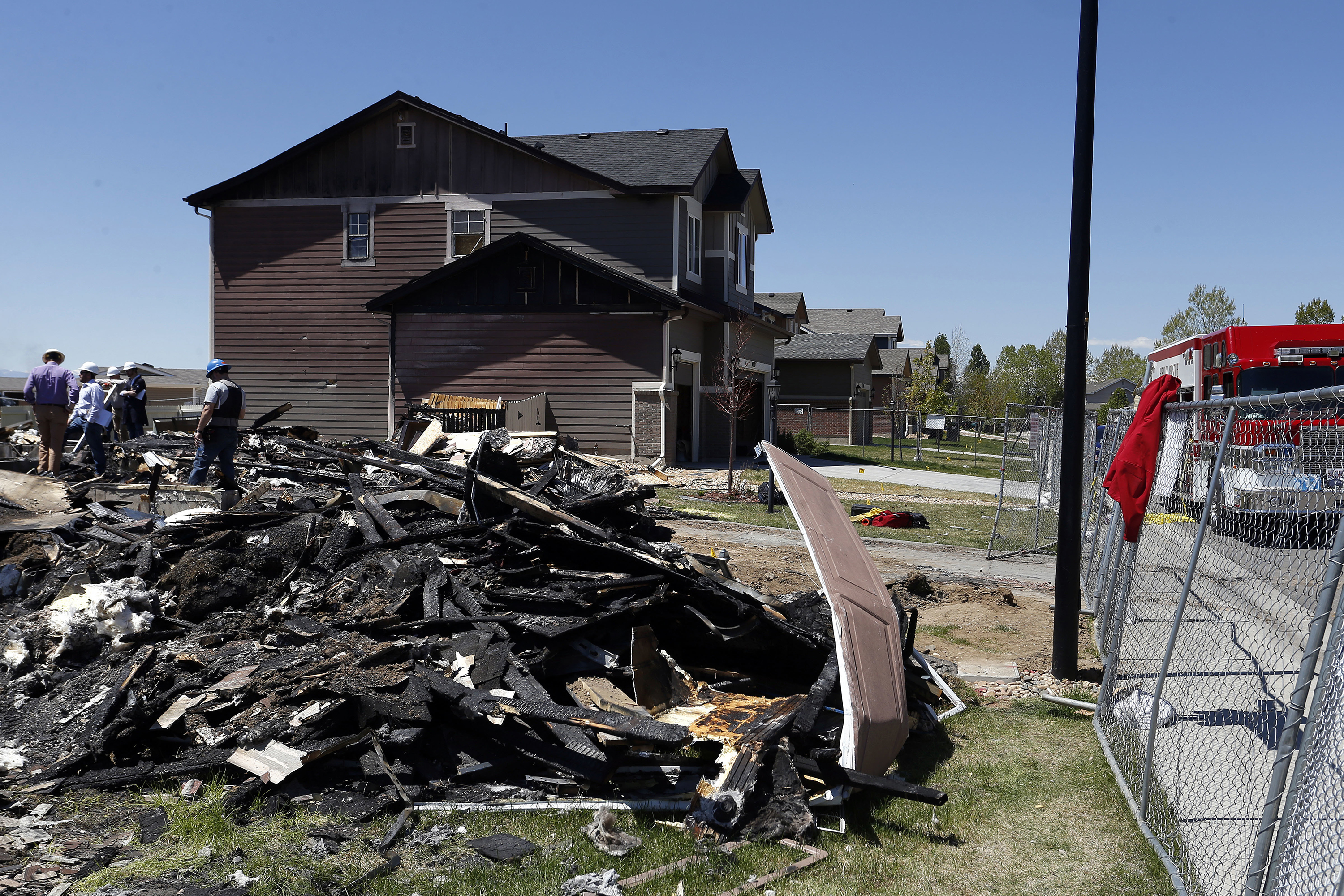 Workers dismantle the charred remains of a home on May 4, 2017 where a gas line leak explosion killed two people inside their home, in Firestone, Colorado.