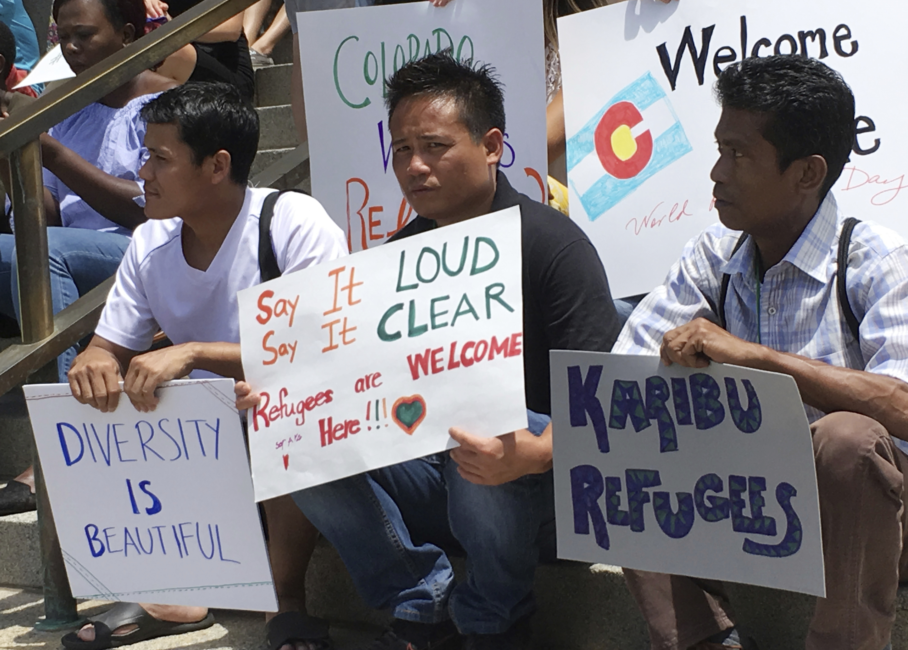 Colorado refugees hold signs during a World Refugee Day rally at the state Capitol in Denver on Tuesday, June 20, 2017.