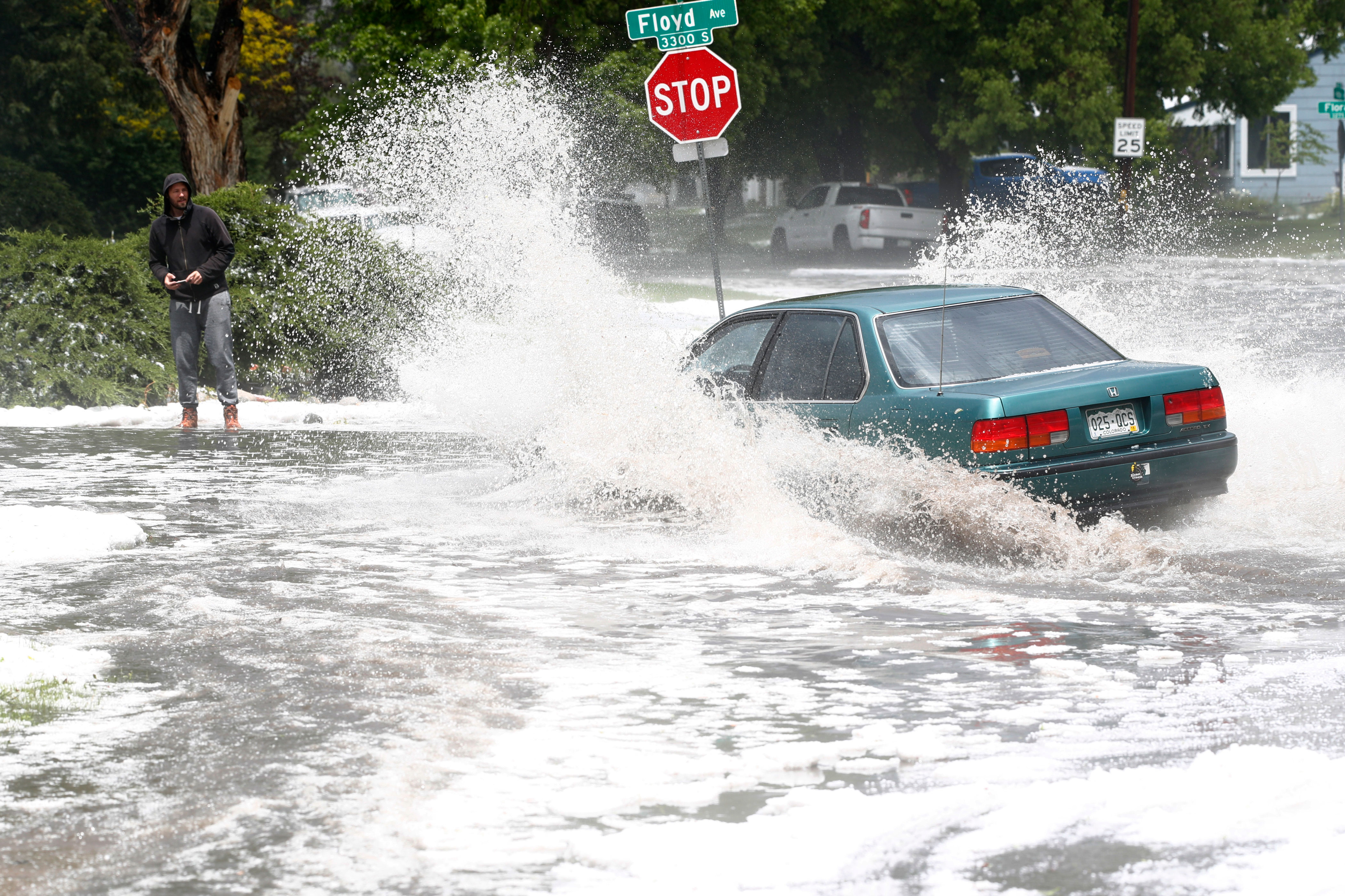 <p>A pedestrian looks on as a motorist guides a car through an intersection swamped by heavy rain and hail in southeast Denver, May 14, 2018, after ahigh-powered storm swept over the area.</p>