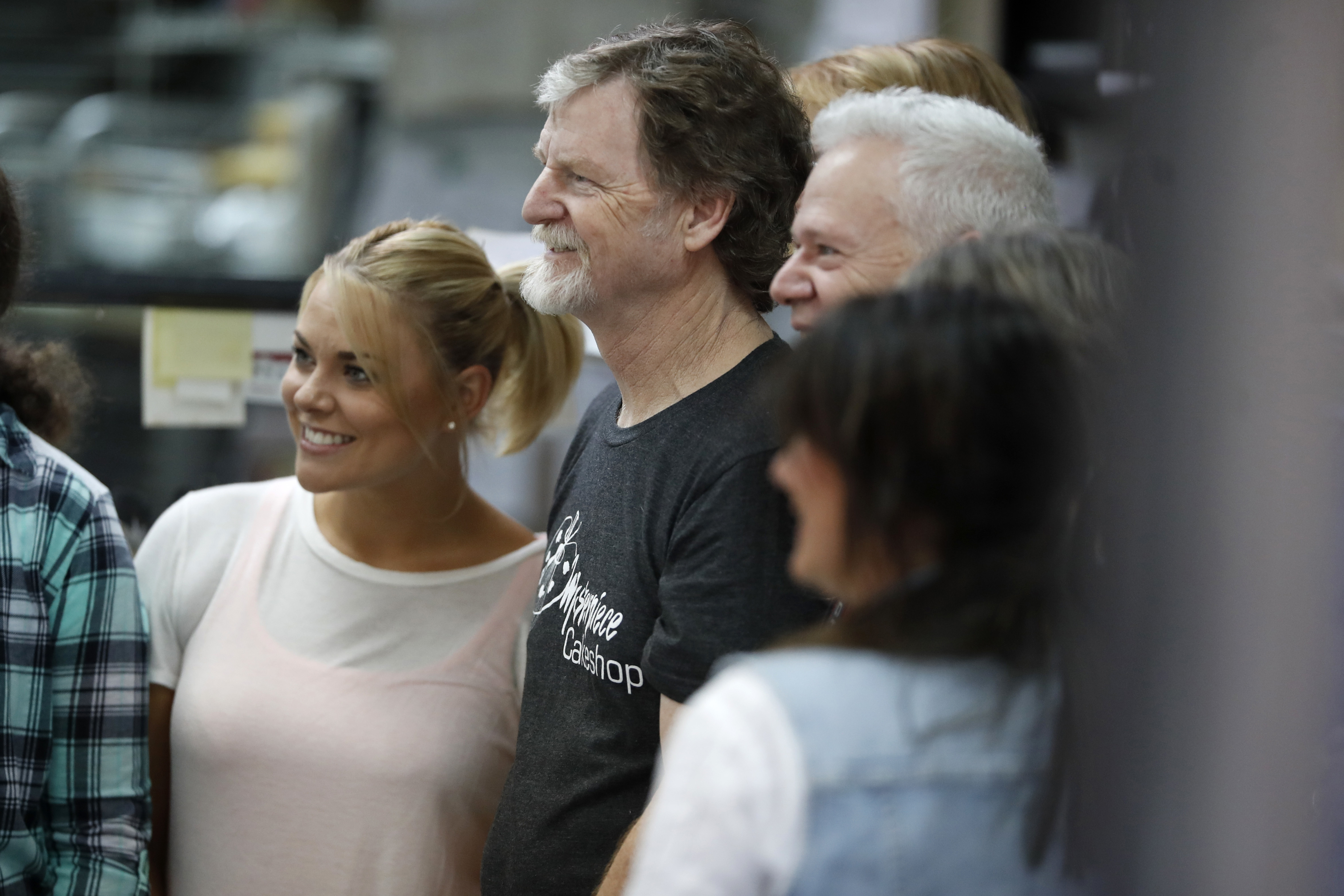 Baker Jack Phillips, center, owner of Masterpiece Cakeshop, is surrounded by supporters for a cellphone photo inside his shop after the U.S. Supreme Court ruled in his favor, Monday, June 4, 2018.