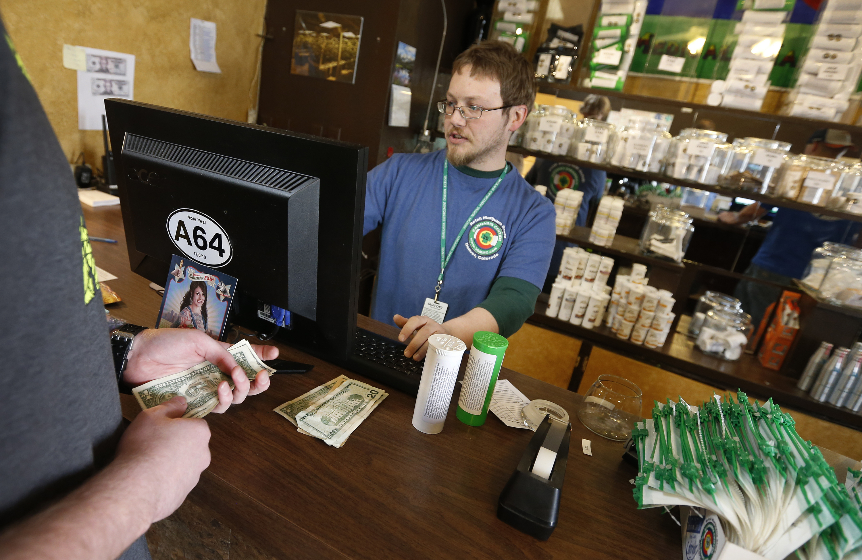 A customer pays cash for retail marijuana at 3D Cannabis Center, in Denver, May 8, 2014.