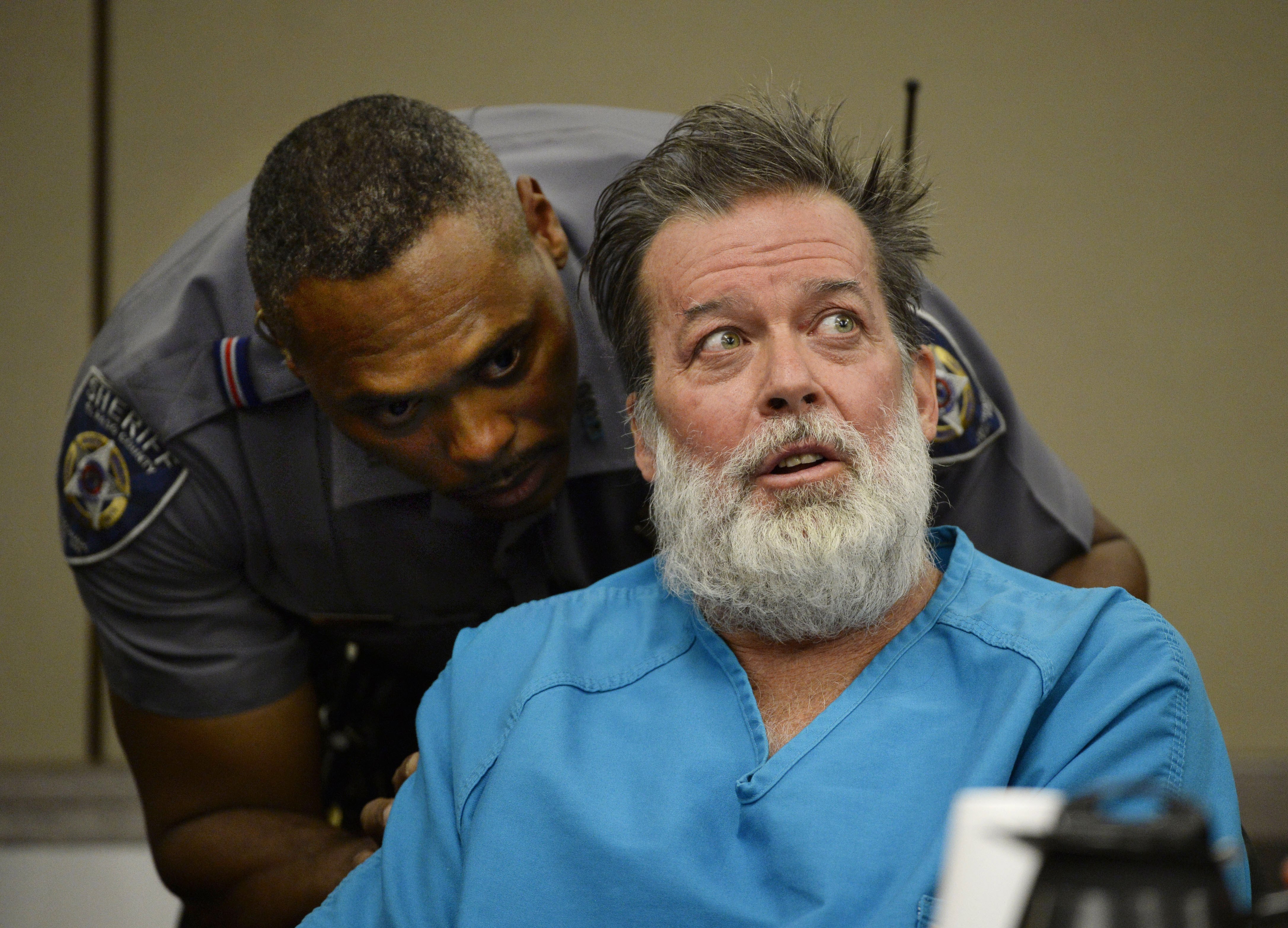 An El Paso County Sheriff's deputy talks to Robert Lewis Dear during a court appearance on Wednesday, Dec. 9, 2015, in Colorado Springs.