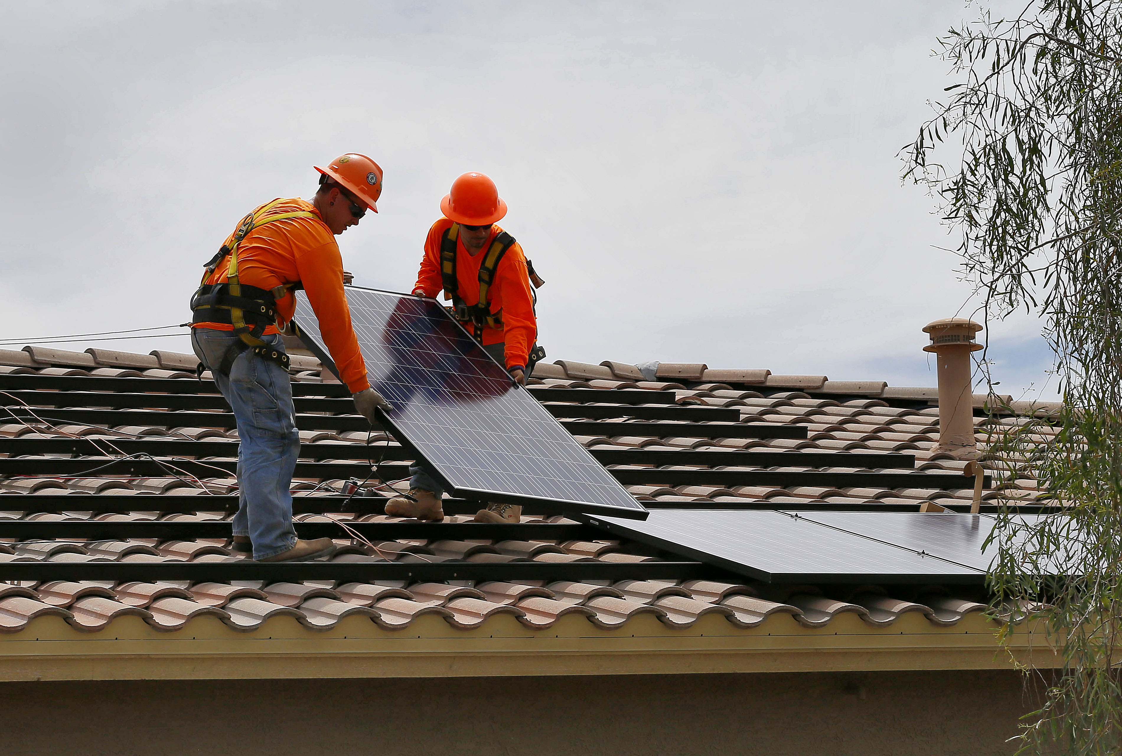 <p>In this July 28, 2015, photo, electricians Adam Hall, right, and Steven Gabert, install solar panels on a roofin Goodyear, Ariz.</p>