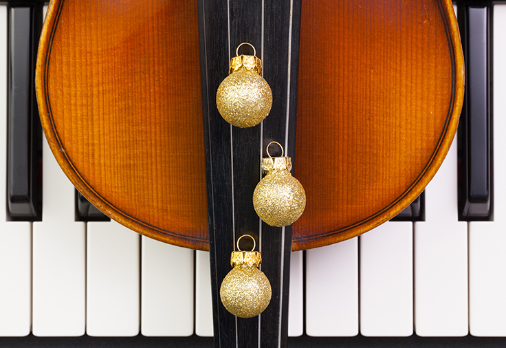 Close up shot of a piano keyboard with a violin and gold bulb ornaments on top