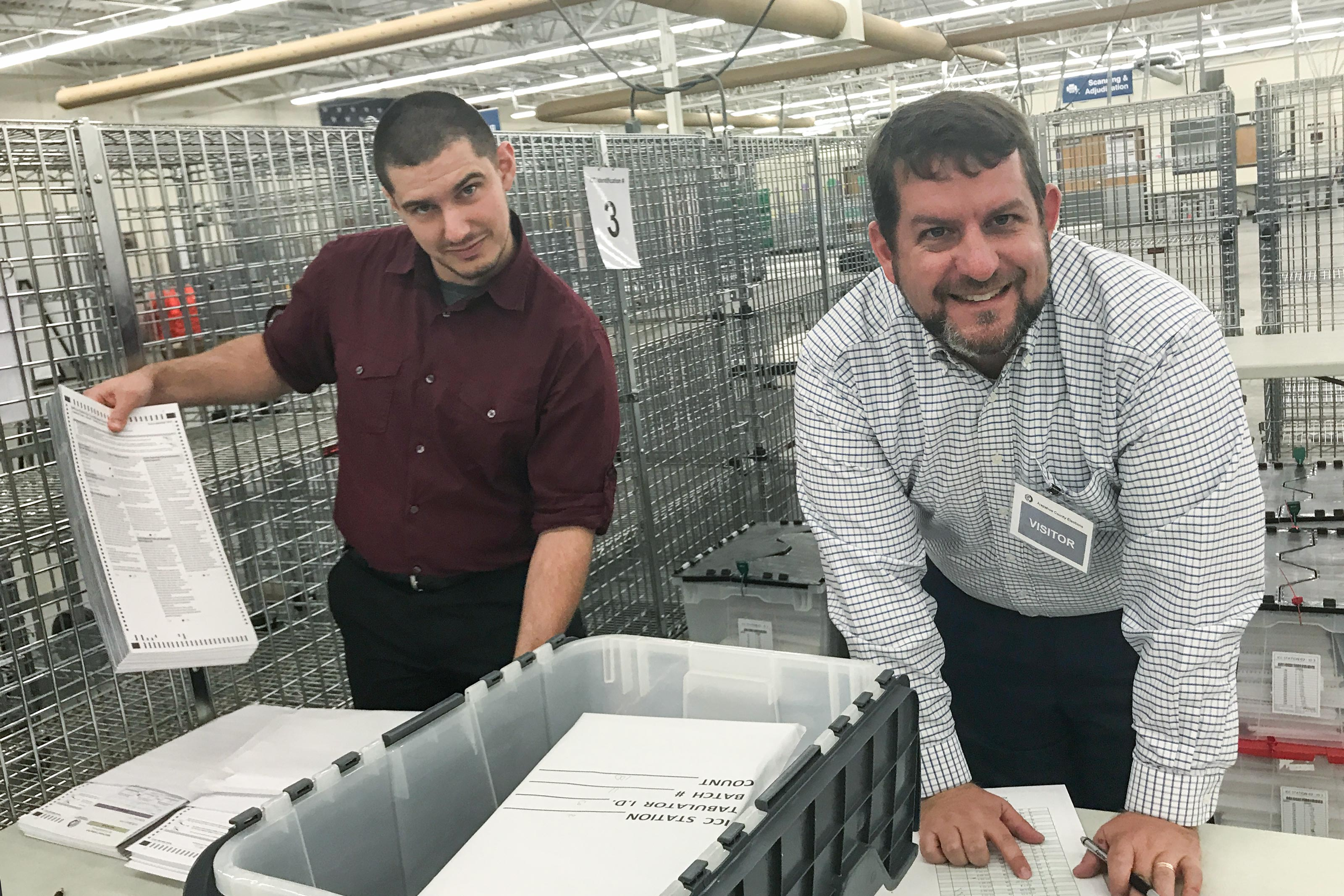 <p>Arapahoe County Clerk staffer Caleb Hendrich, left, and U.S. Election Commissioner Matt Masterson begin the process of pulling ballots to be audited at the Arapahoe County election warehouse.</p>