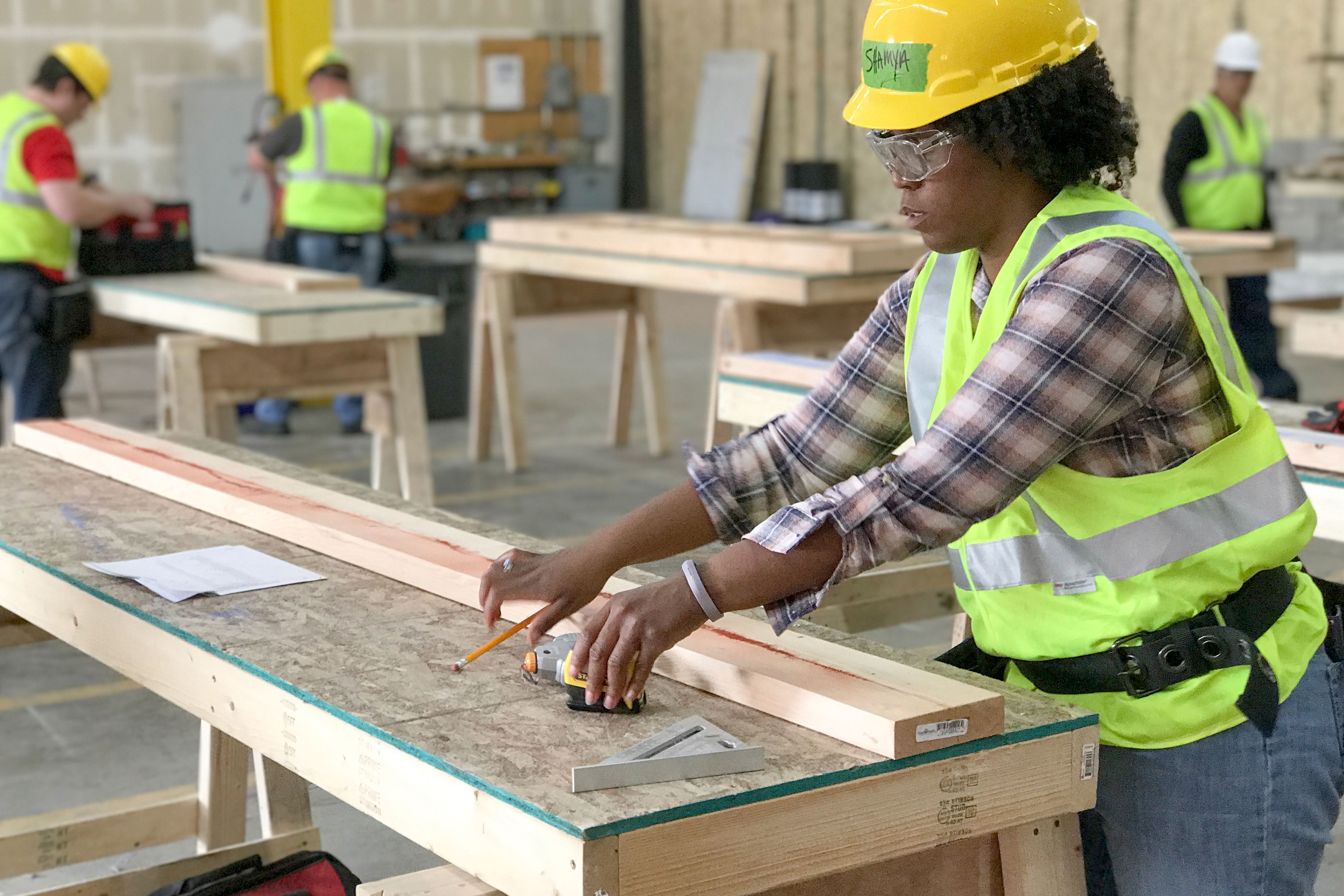 """<p>Shimai Hunter works on a 2""""x4"""" at the Colorado Homebuilding Academy. She wants to get into the construction industry in hopes of better pay and a more flexible schedule.</p>"""