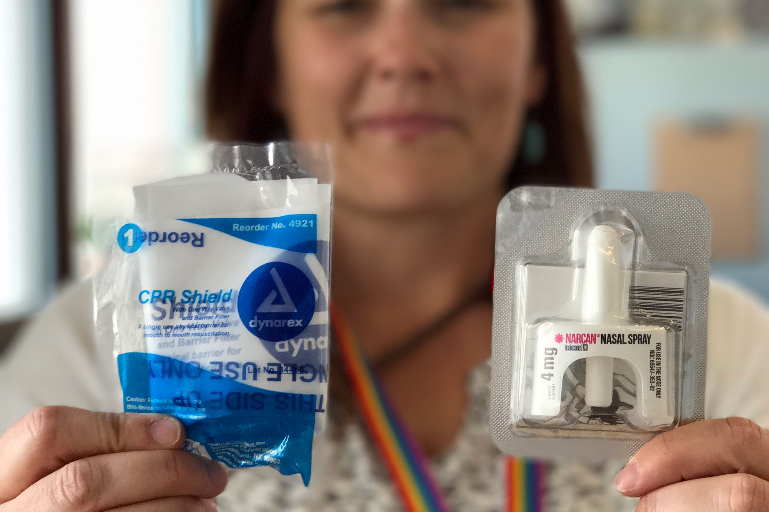 <p>Elissa Hardy, a social worker at the Denver Public Library, holds up a CPR mask and a bottle of Narcan. The medicine is used to reverse an opioid overdose.</p>