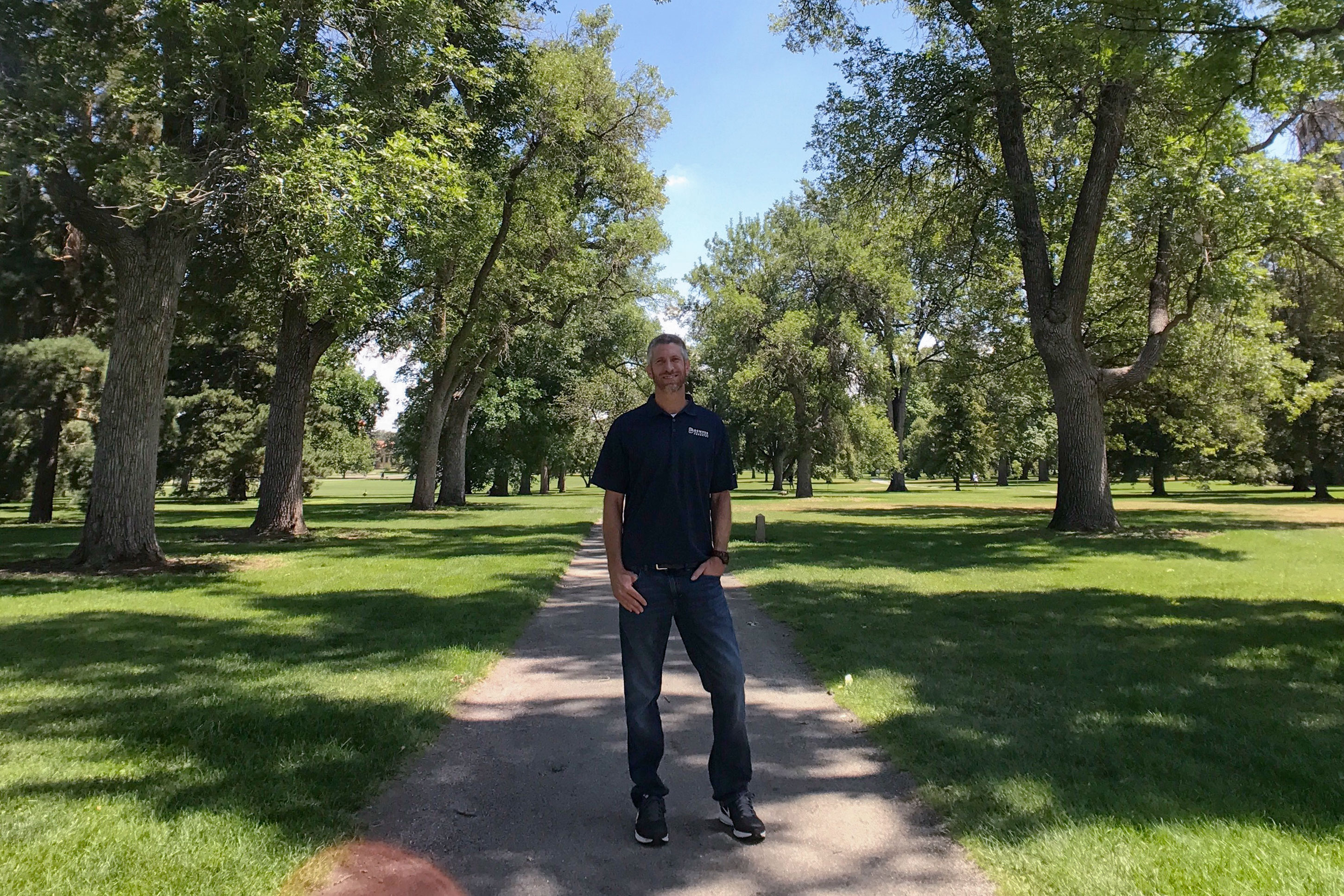 <p>Denver city forester Rob Davis stands amongst a row of ash trees in City Park. These trees will be treated to prevent an Emerald Ash Border infestation.</p>