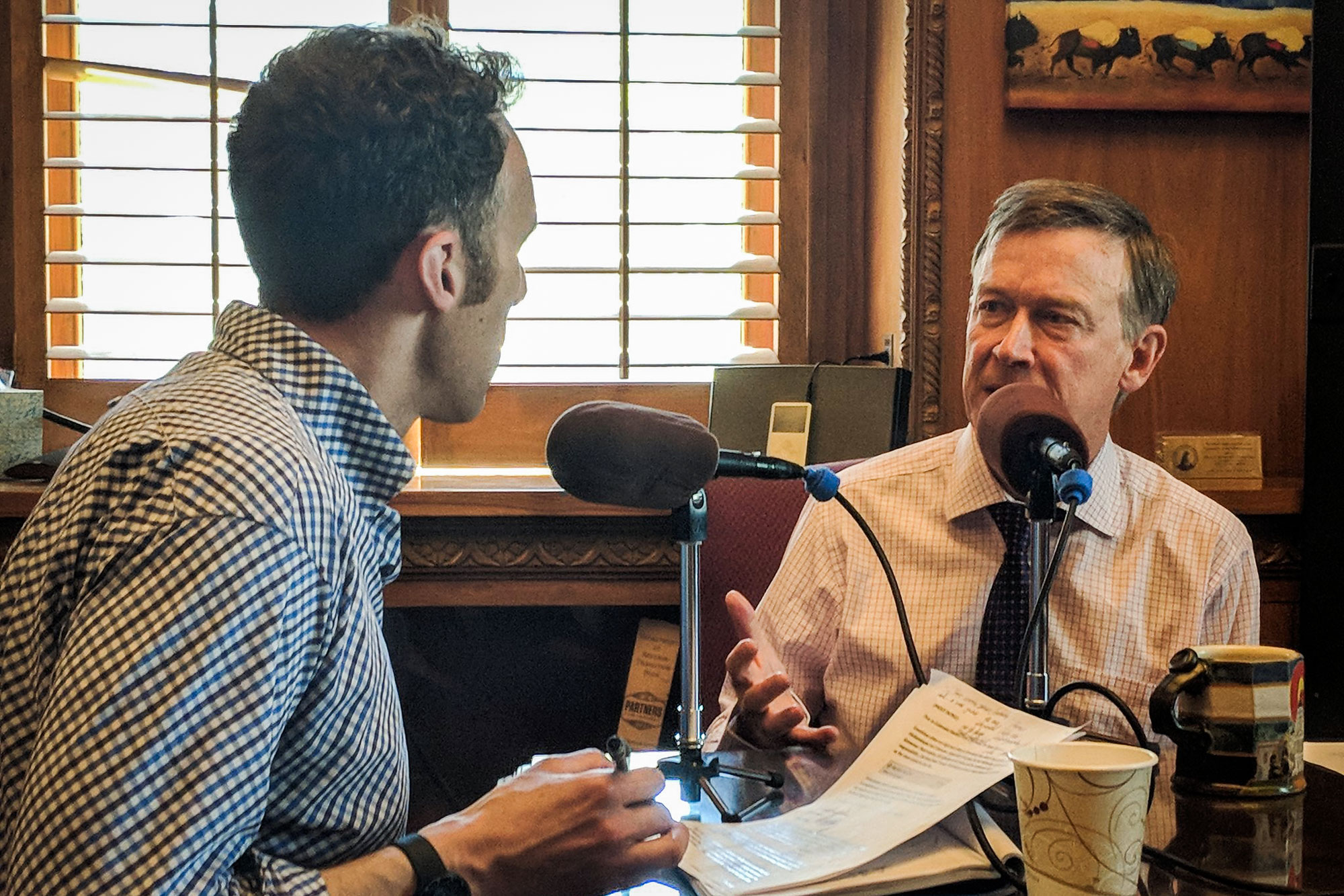 <p>Colorado Matters host Ryan Warner, left, interviews Gov. John Hickenlooper in his office at the Capitol, May 16, 2018.</p>