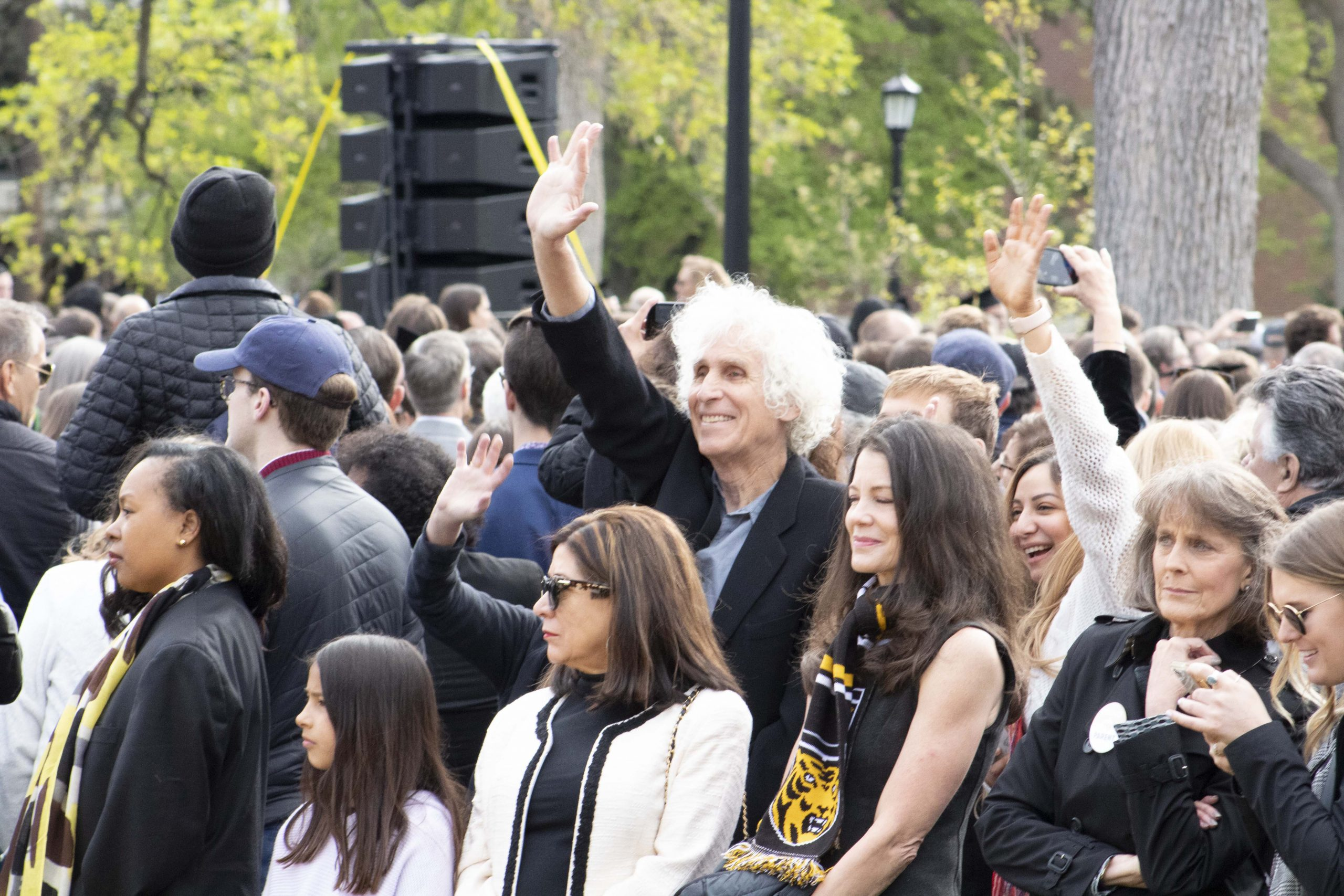 Family and friends excitedly wave to graduates at teh 2019 Colorado College Commencement.