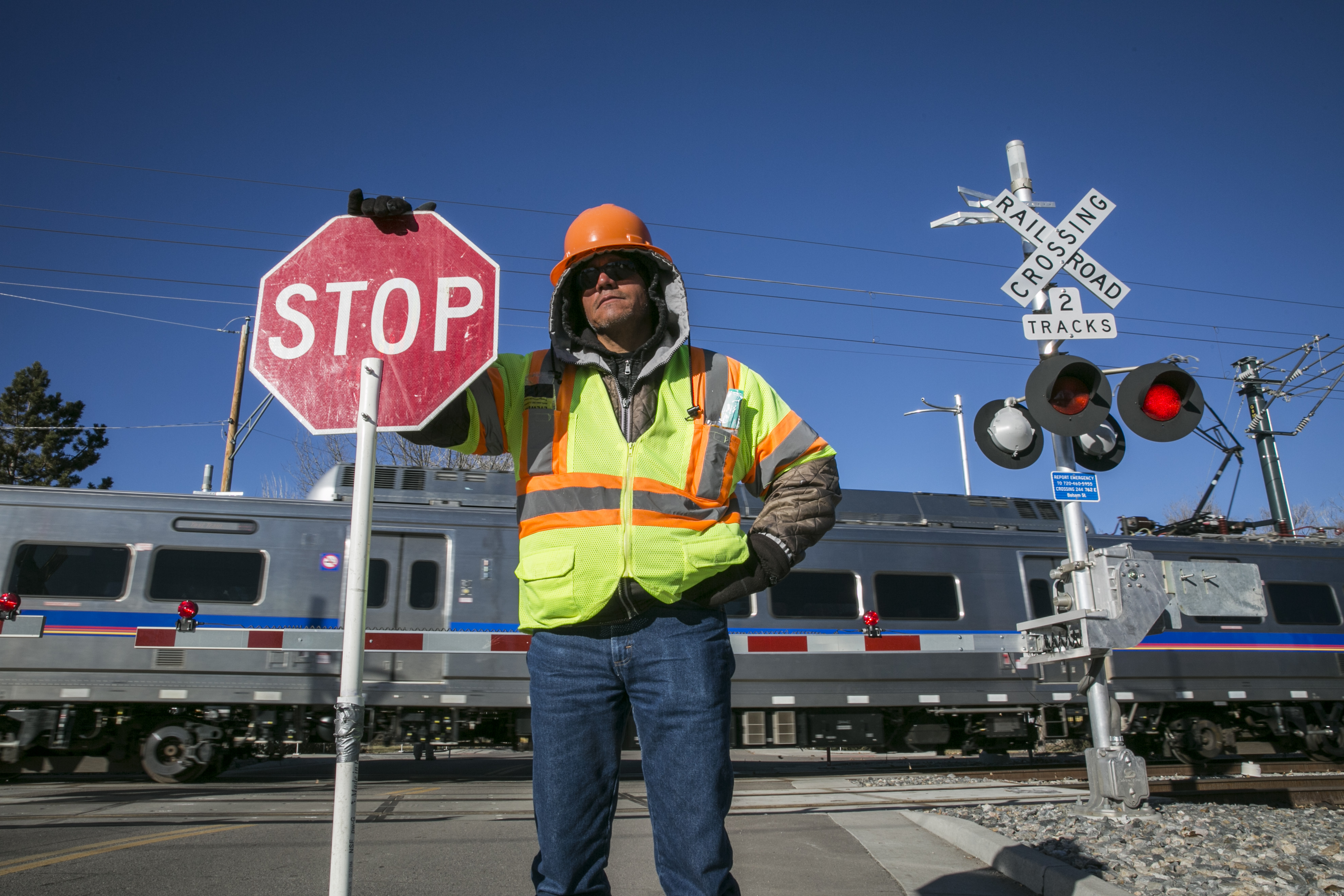 <p>A flagger stands in front of a G Line crossing in Arvada, Colorado in January 2018.</p>