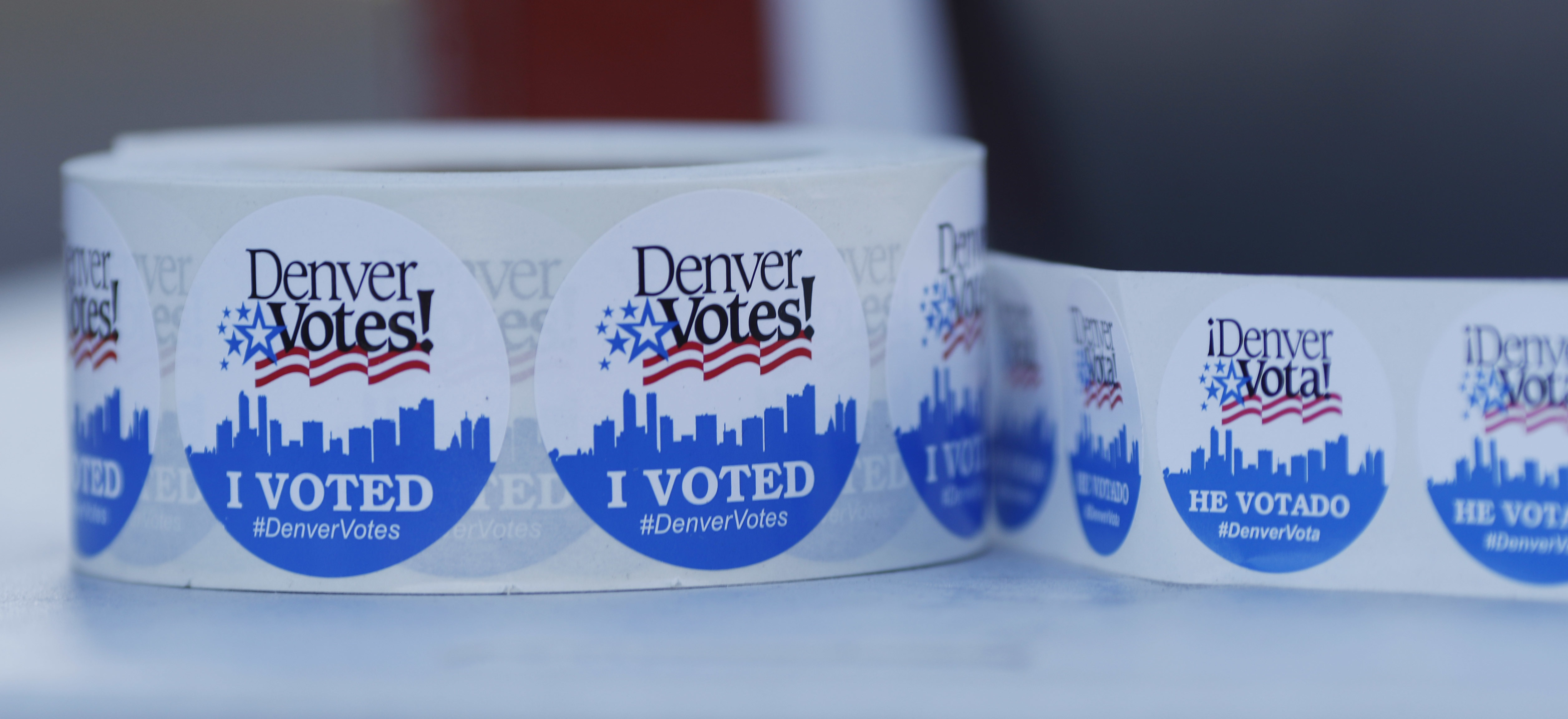 <p>A roll of stickers in English and Spanish awaits distribution to voters dropping their ballots off at the Denver Election Commission, Nov. 8, 2016.</p>