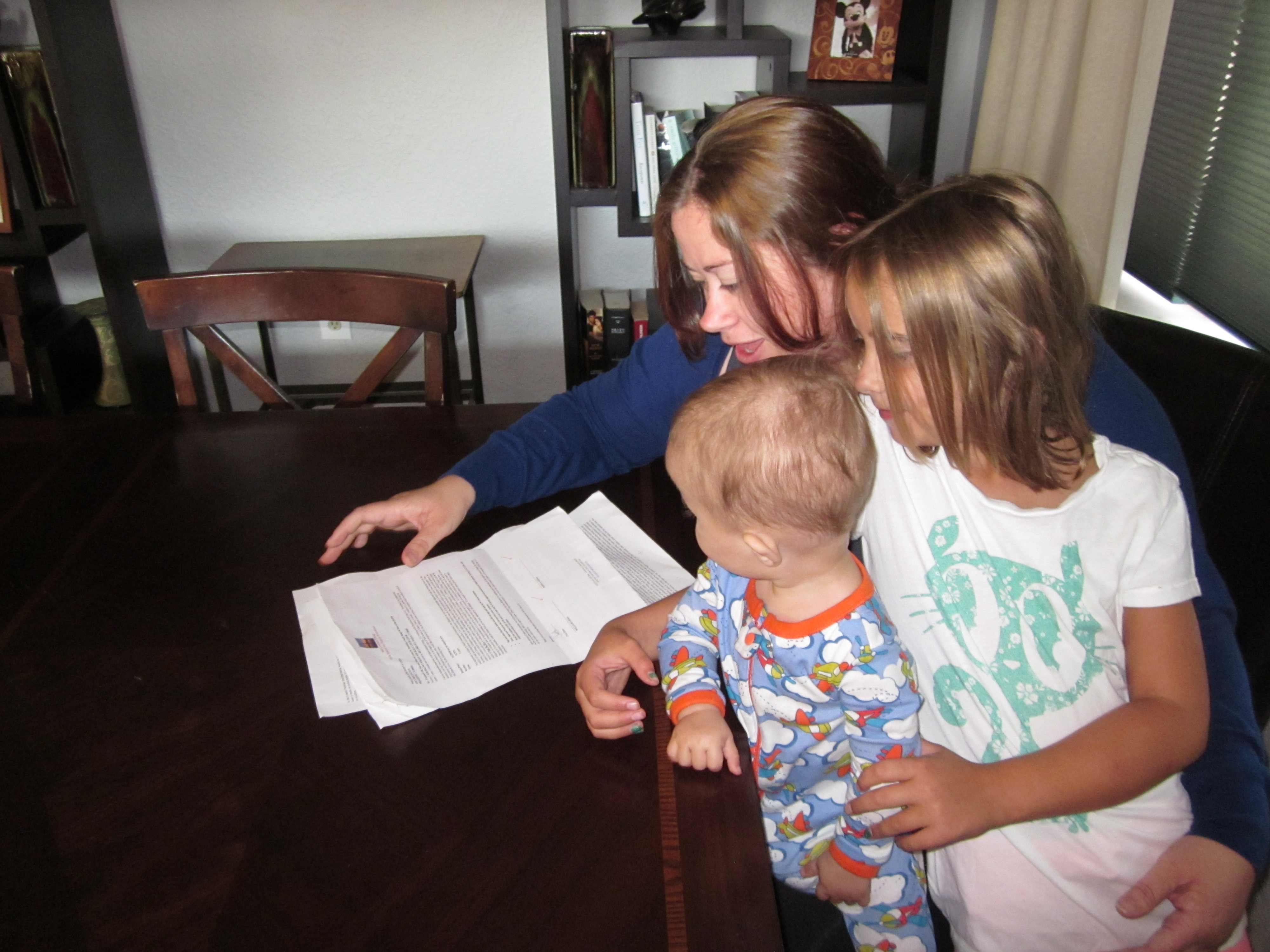 <p>Dawn Gioia and her children read over an oil and gas lease from Mid Continent Energy to drill underneath her home in Brighton, Colo.</p>