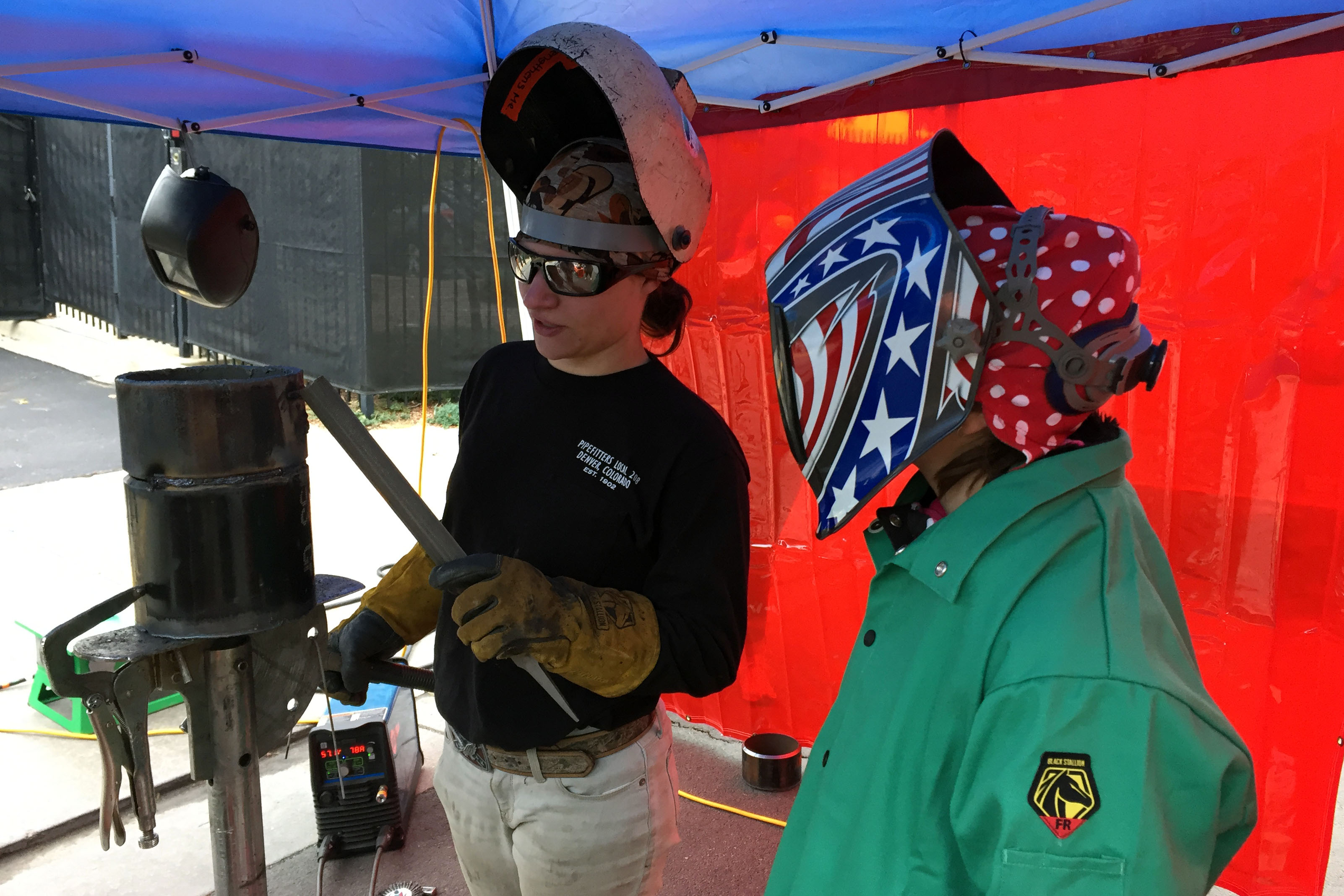 """<p>Rachel Neeb (left), a second-yearpipefitting apprentice, shows 12-year-old RaynaJeannelle(right) how to weld. The two were attending the Transportation and Construction Girl career fair at the<span style=""""color: rgb(64, 69, 64);"""">Renaissance Hotel Stapleton in Denver. The annual event exposes young girls and teenagers to jobs in male-dominated fields.</span></p>"""