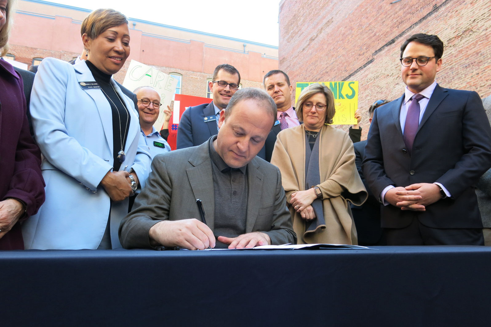 <p>Gov. Jared Polis signs his first environmental executive order on Thursday, Jan. 17, 2019,to put more electric cars and buses on the road. He's flanked by state representatives and leaders of environmental groups.</p>